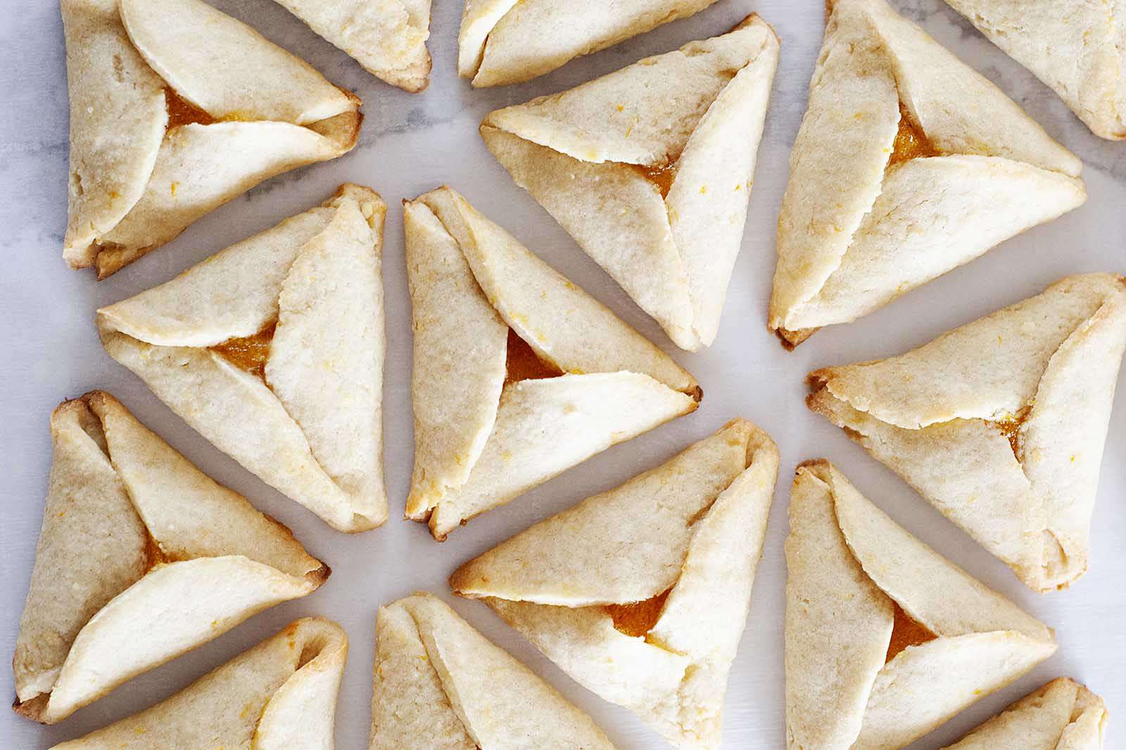 Horizontal photo of Apricot Hamantaschen set in a circular pattern on a white surface.