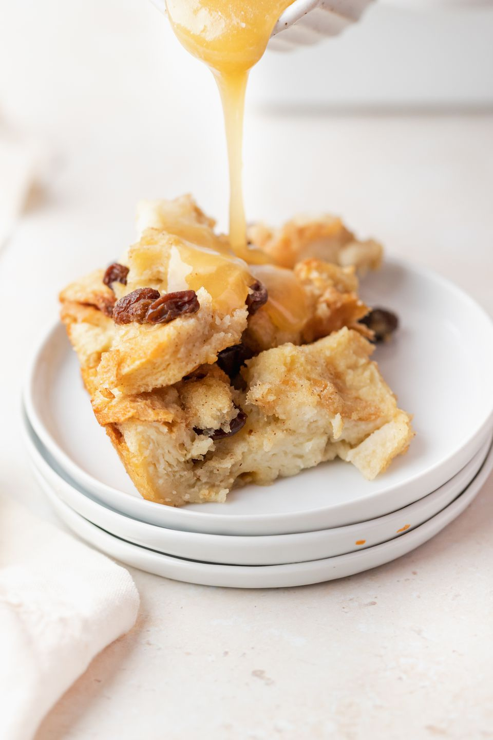 Pouring bread pudding sauce over a plate of bread pudding.