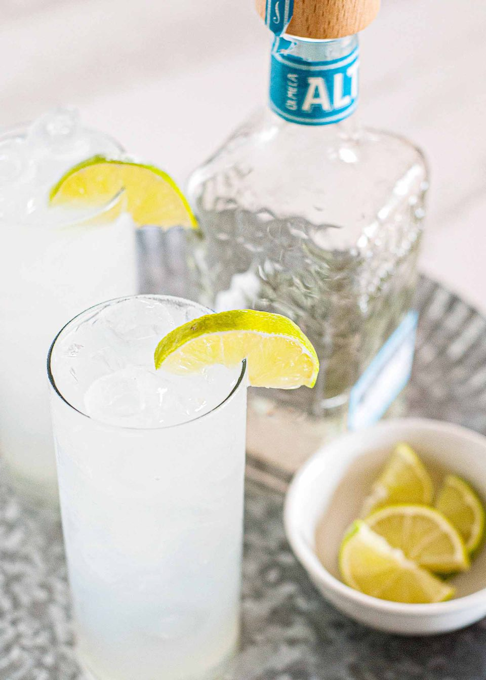 Spicy Paloma Cocktail Recipe - tall glass of tequila paloma cocktail with bottle and limes