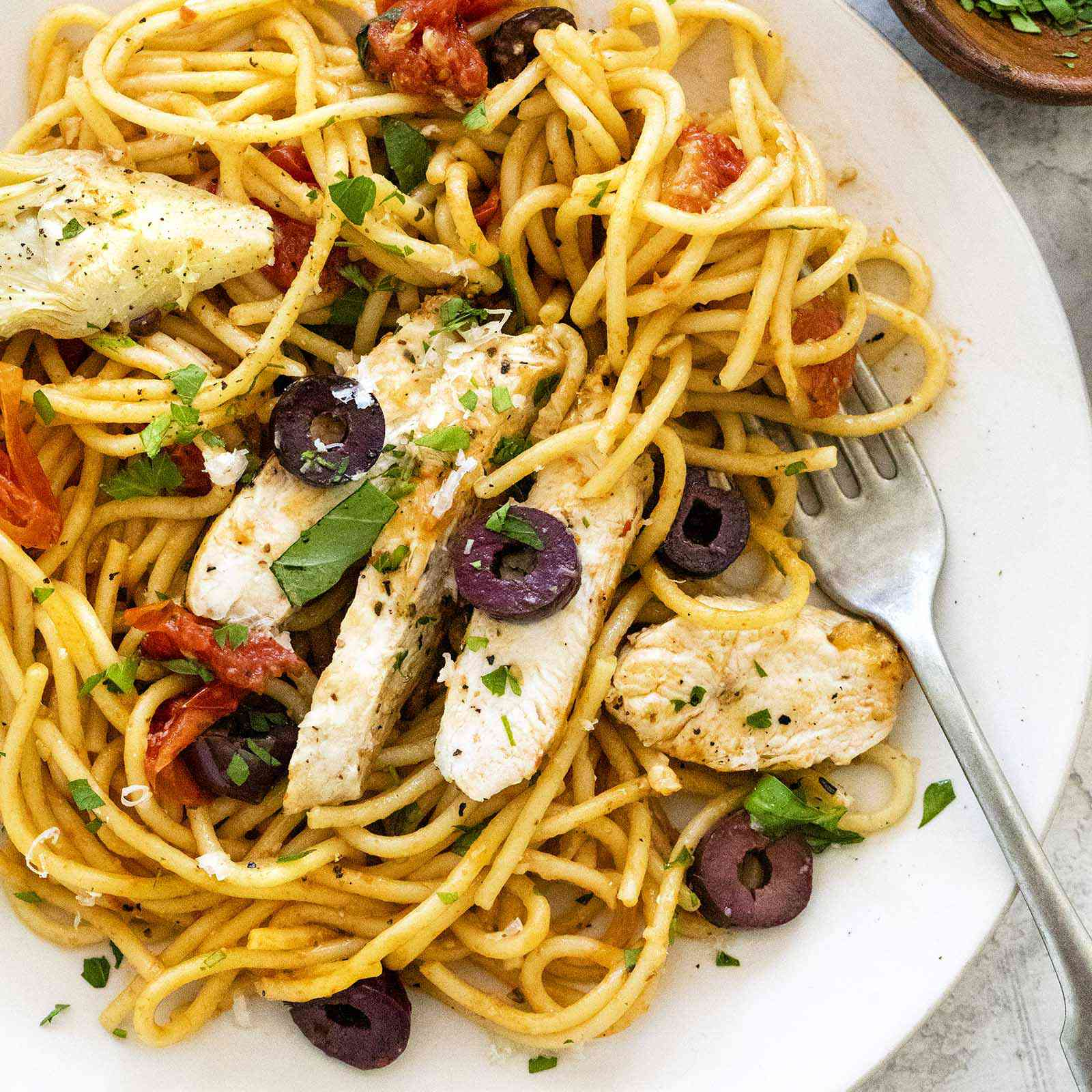 Overhead view of a plate of chicken pasta skillet dinner. Spaghetti, sliced chicken, olives and tomatoes are mixed together on a white plate along with a fork.