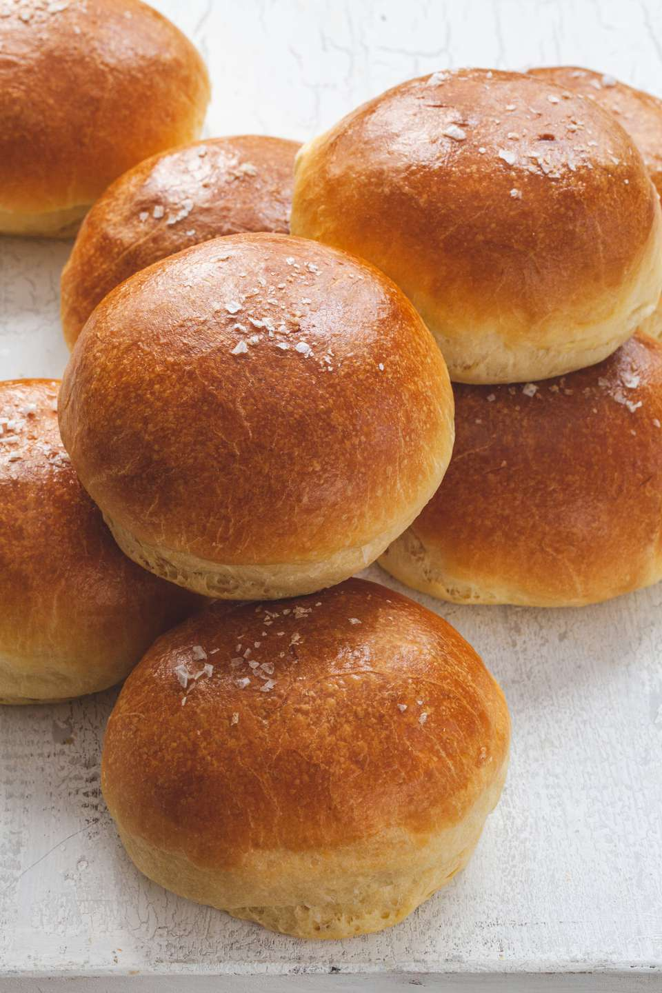 The Fluffiest Brioche Buns stacked on a counter.