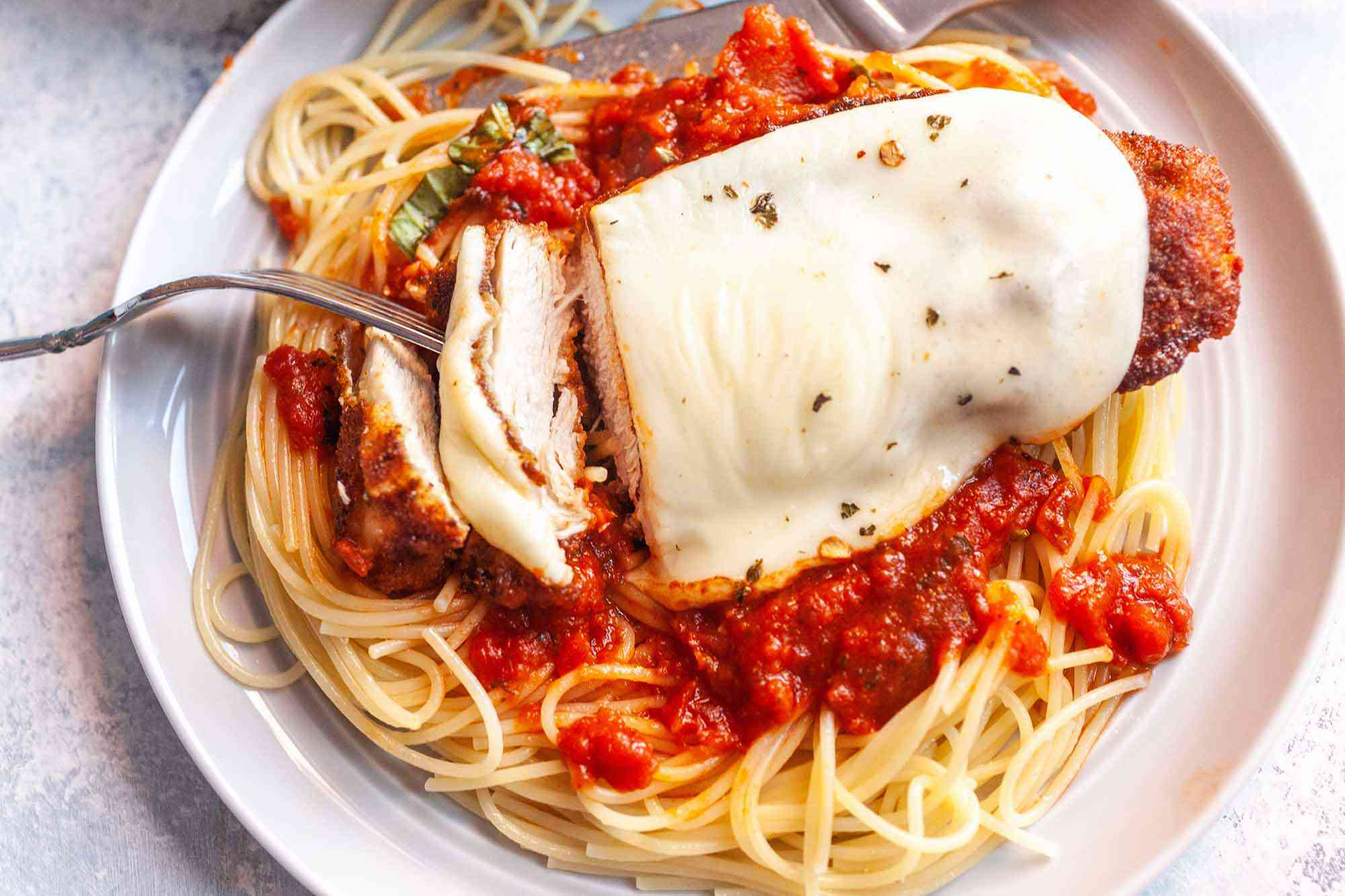 Baked Chicken Parmesan in a Skillet serve over spaghetti