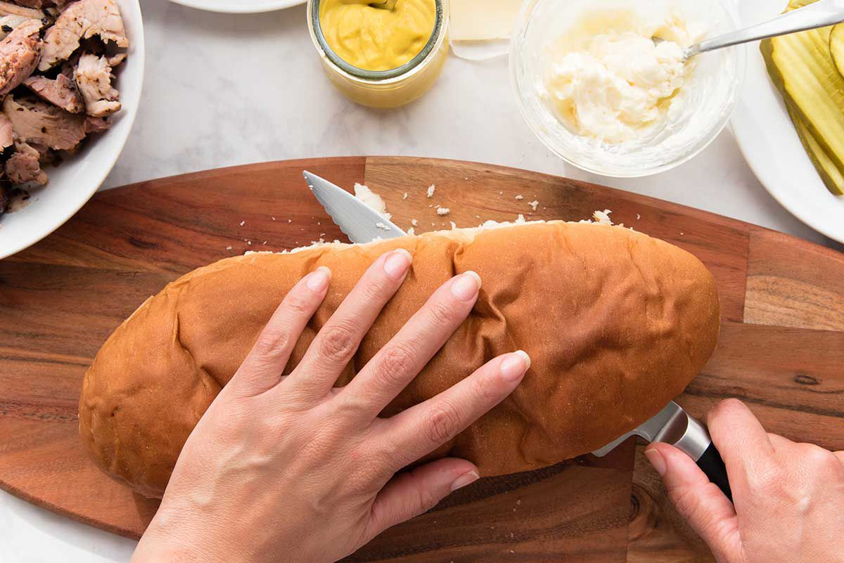 A loaf of french bread being sliced horizonally with a chefs knife. One hand rests on top of the loaf. Shredded pork, a glass container of mustard, a small glass bowl of mayonnaise and a partial plate of sliced pickles is visible above.