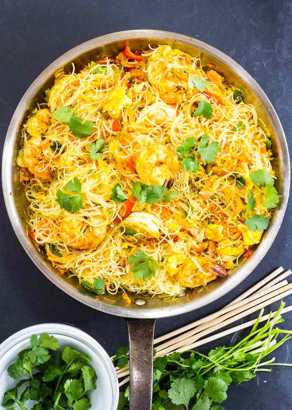 Singapore Style Noodles with Shrimp and cilantro in a skillet with chopsticks nearby