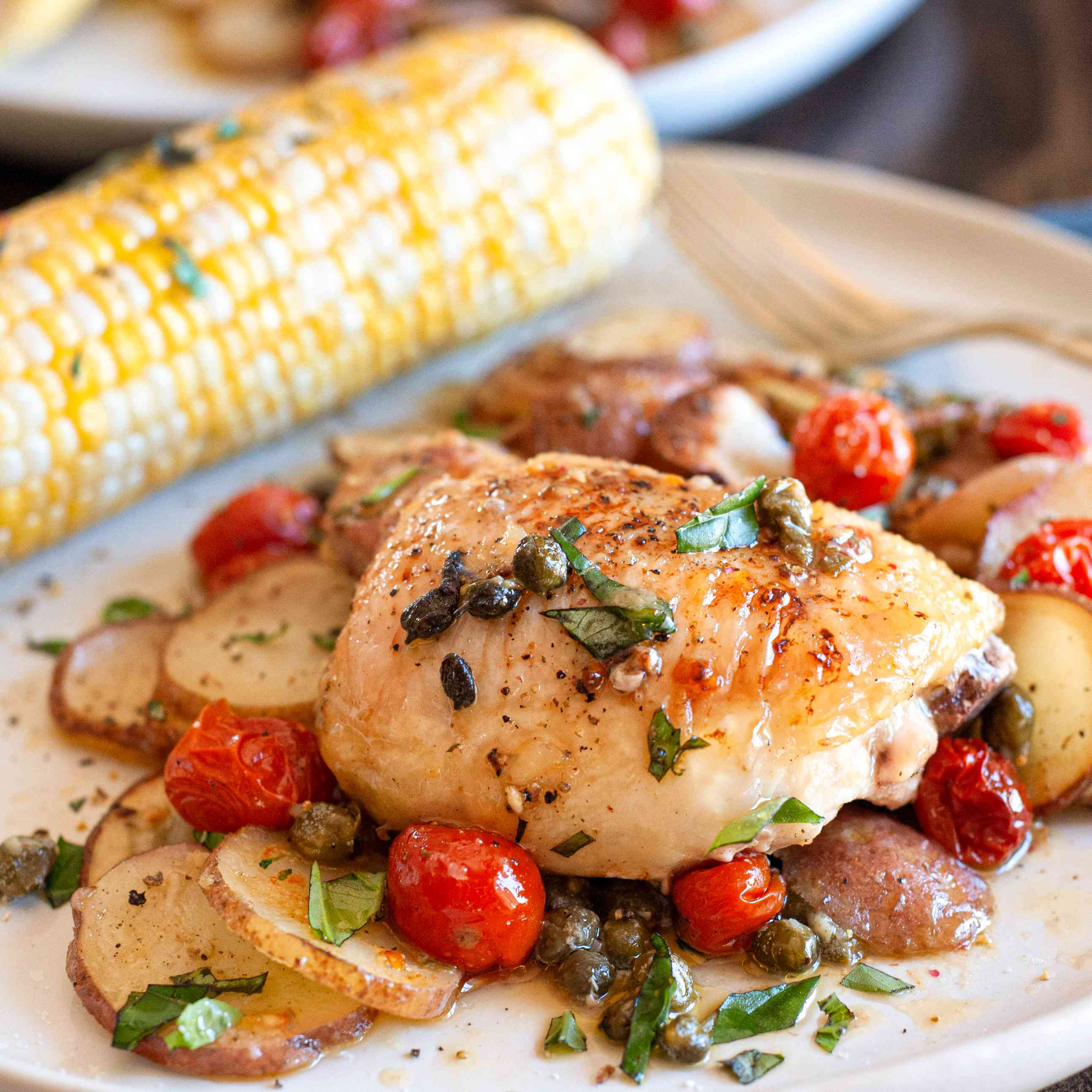 A plate of lemon chicken thighs with potatoes, tomatoes, and capers served with corn.
