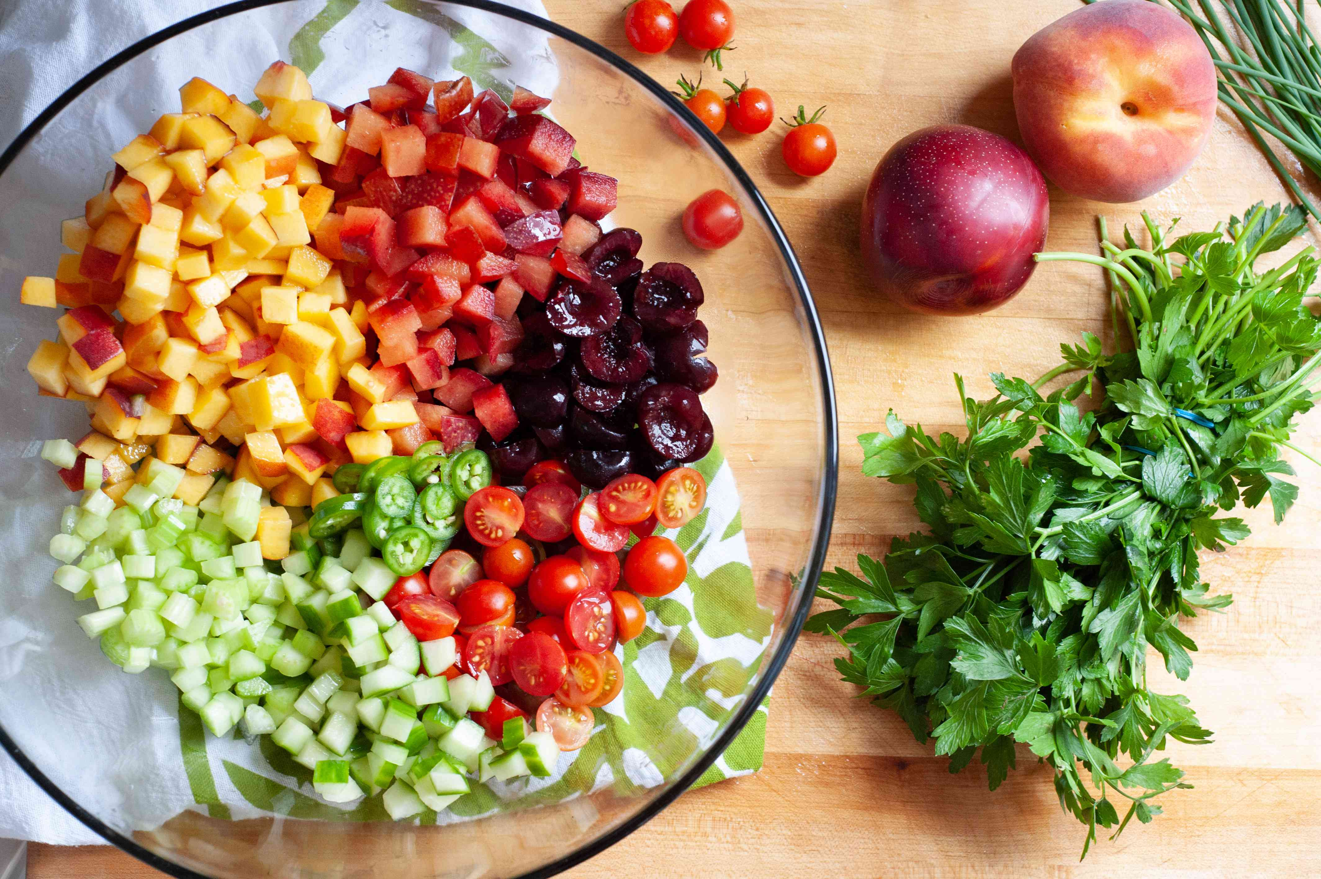 Diced ingredients in a bowl to make an herby fruit salad.