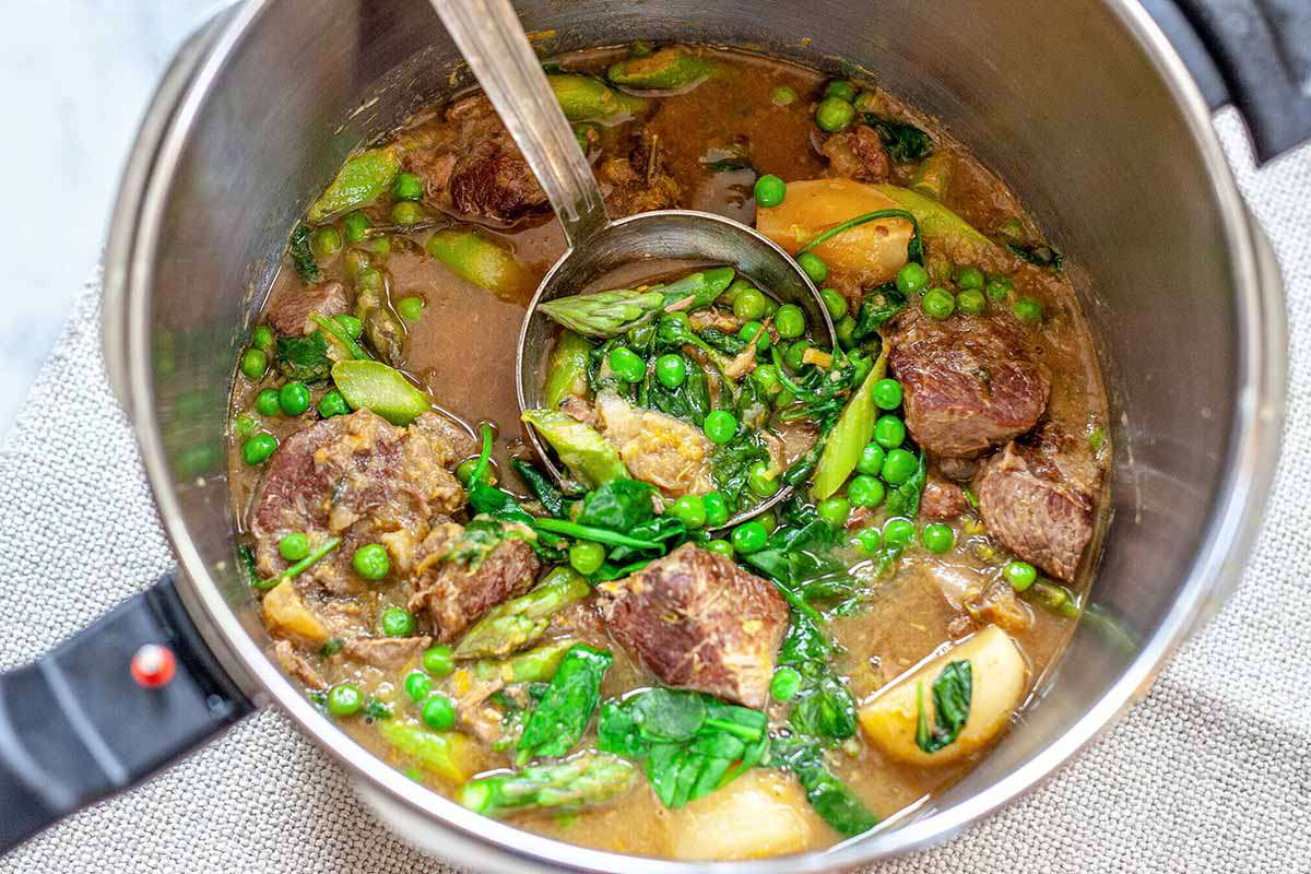 Lamb Stew Recipe - close up of pot of lamb stew with ladle and peas