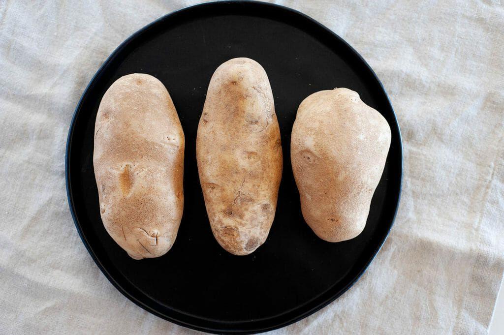 Three russett potatoes on a black tray.