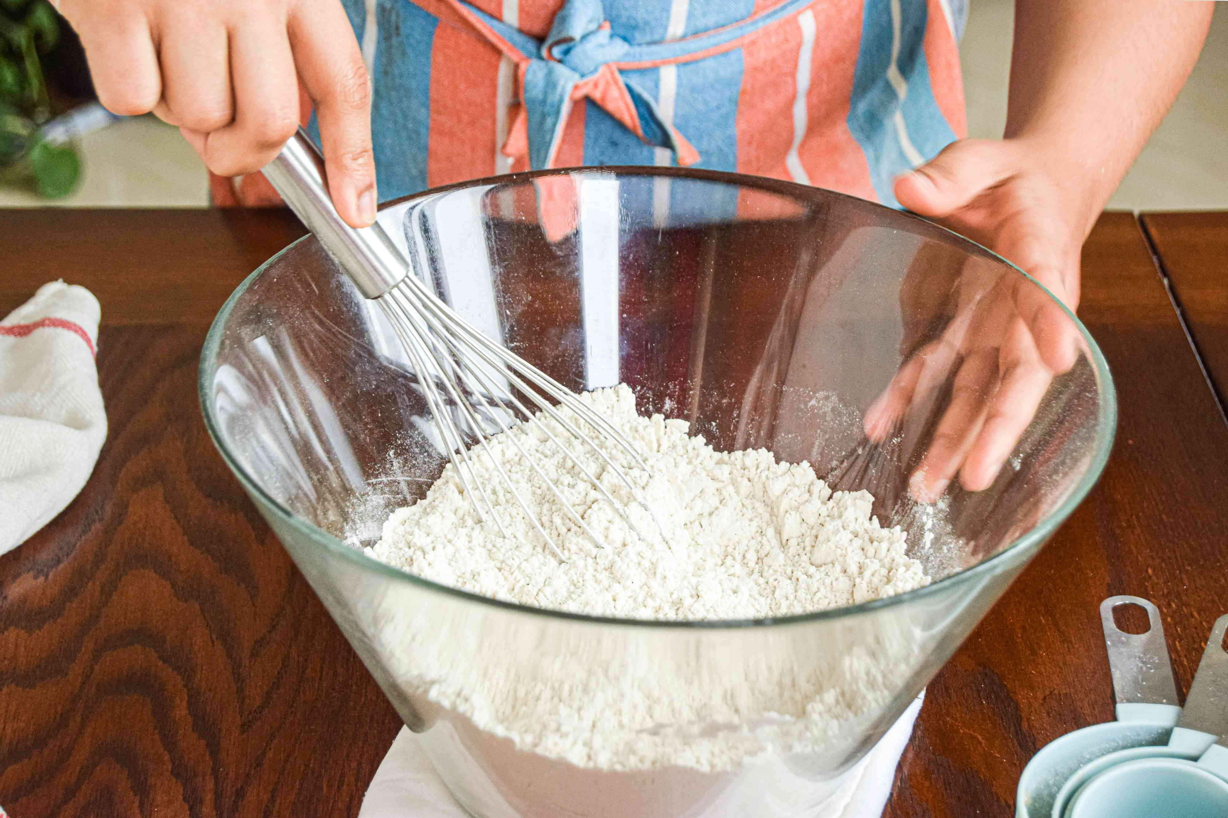 Whisking flour mixture in a bowl to make a hummingbird cake recipe.