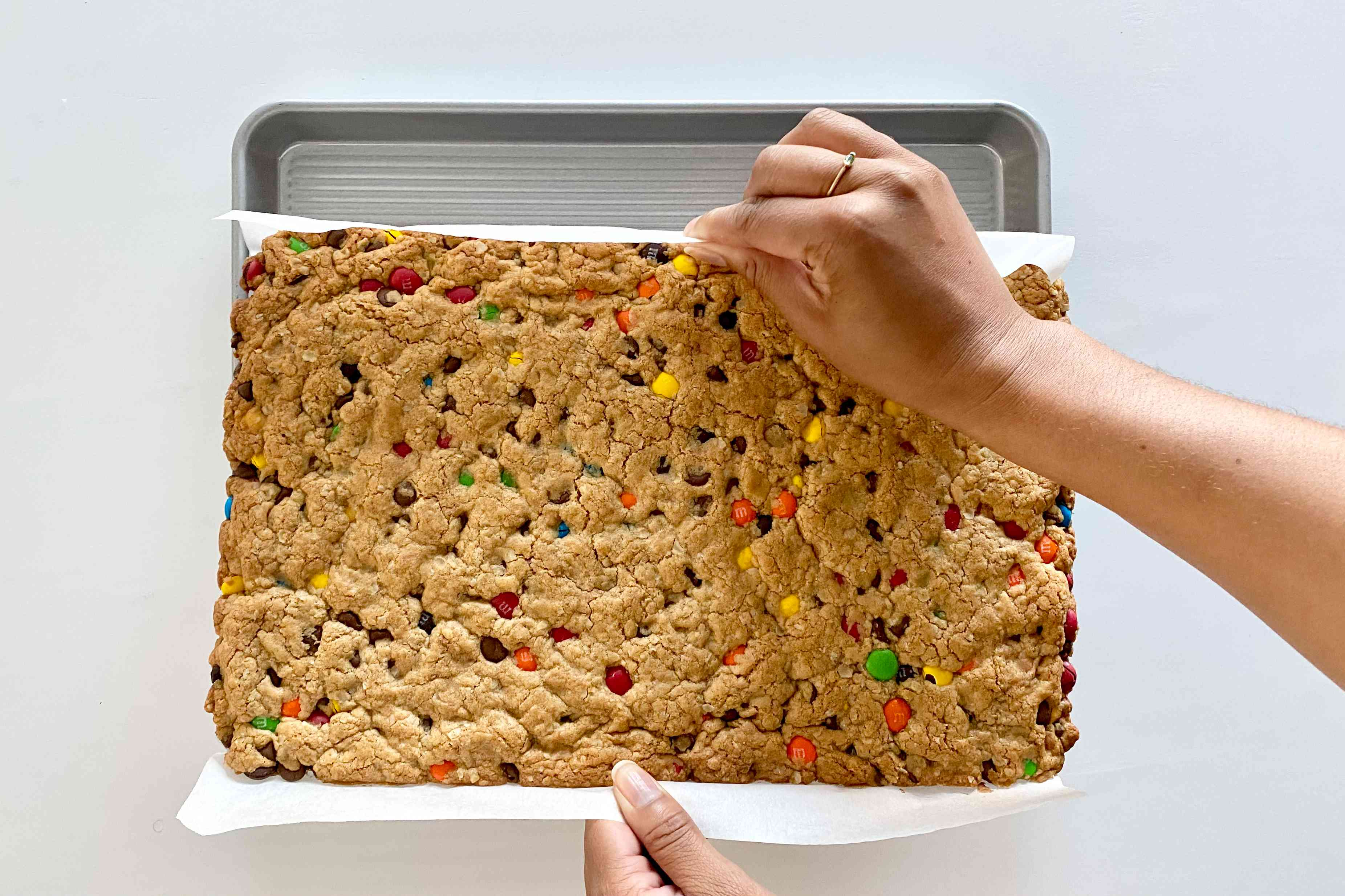 Removing Gluten-Free Sheet Pan Monster Cookies from the pan by holding the parchment.