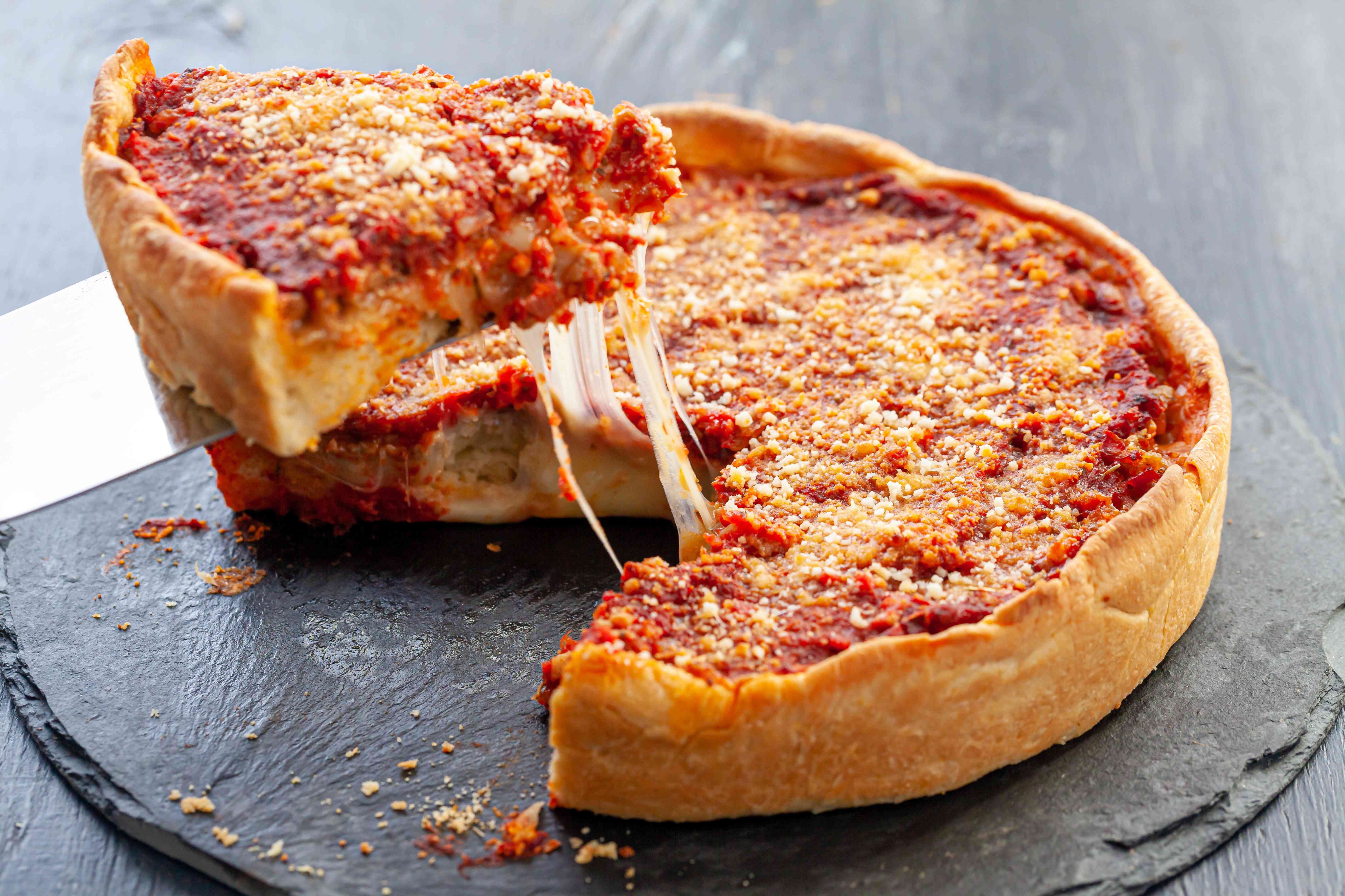 A slice being lifted up from an Italian Sausage Deep Dish Pizza.