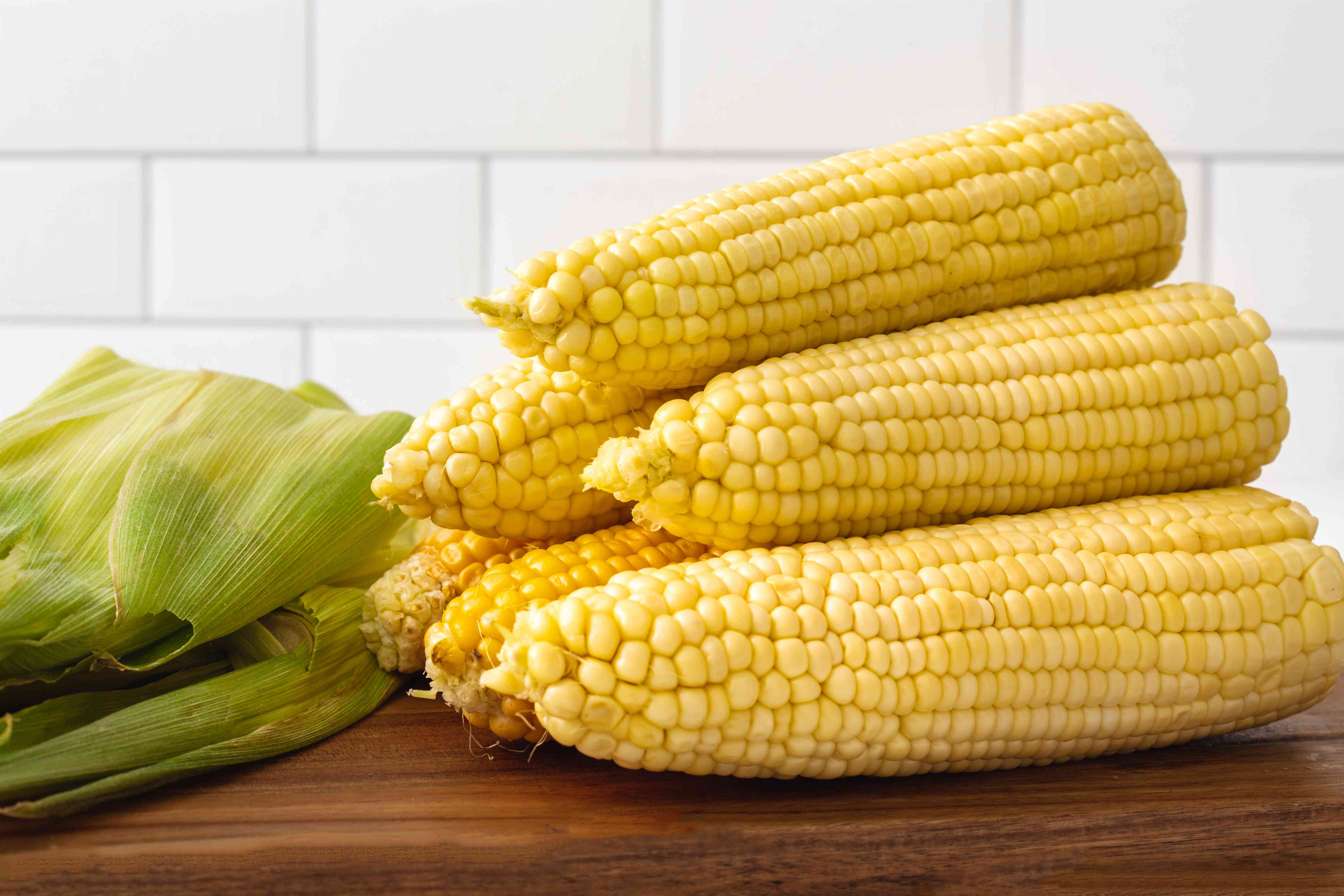 Stacked microwave corn on a cutting board.