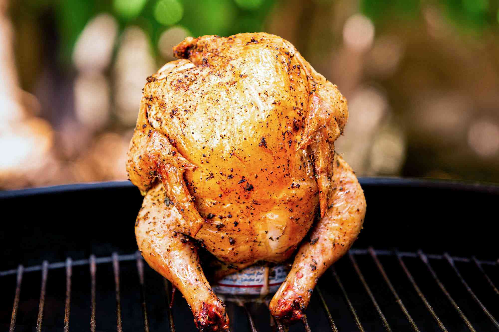 Beer Can Chicken Recipe shown cooked and upright on a grill