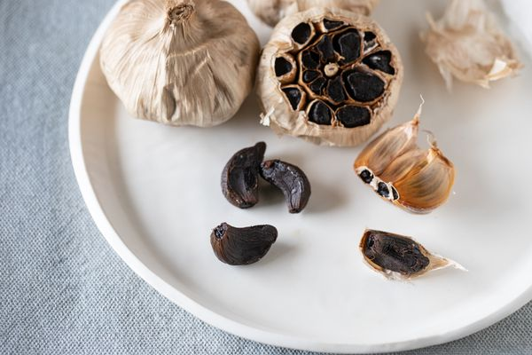 Cloves of black garlic on a white plate with a whole head and a sliced head of garlic behind it.
