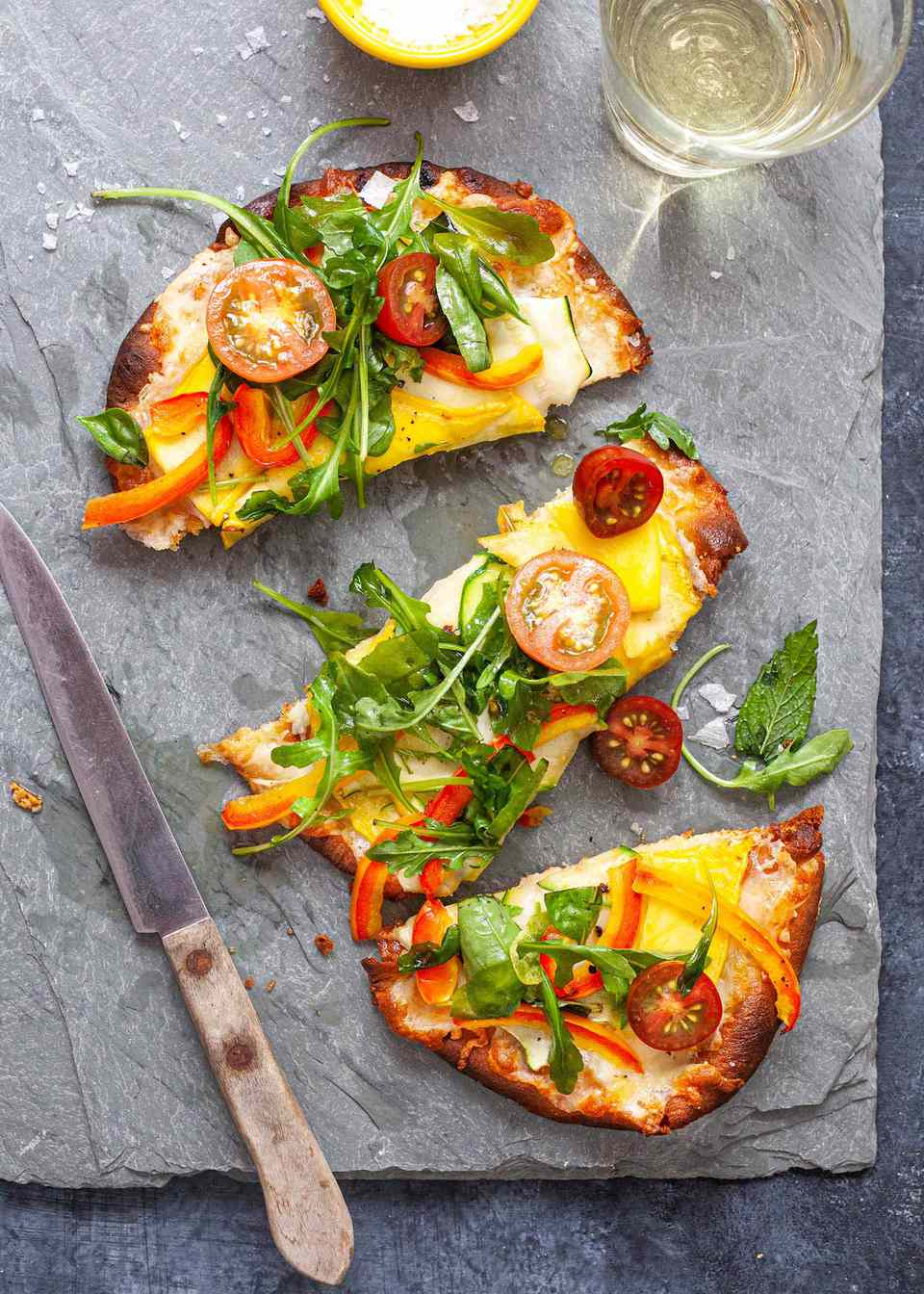 Easy Vegetable Pizza - flatbread pizza piled high with vegetables. Cut into slices on a parchment paper with a wooden handled knife nearby