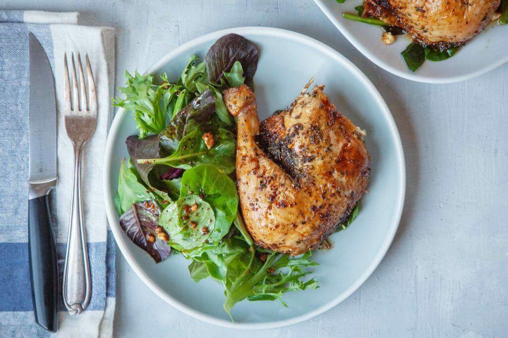 Feta-brined roast chicken leg on a plate with salad greens