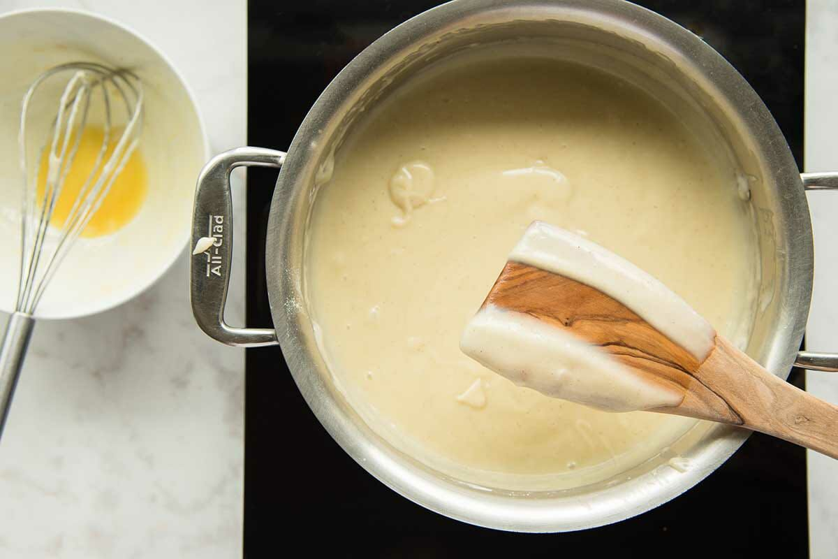 A saucepan of thick custard is on the stove and a wooden spoon is coated in the custard.