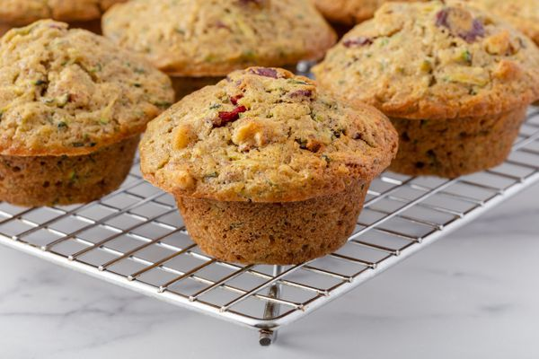 Zucchini muffins cooling on a rack.