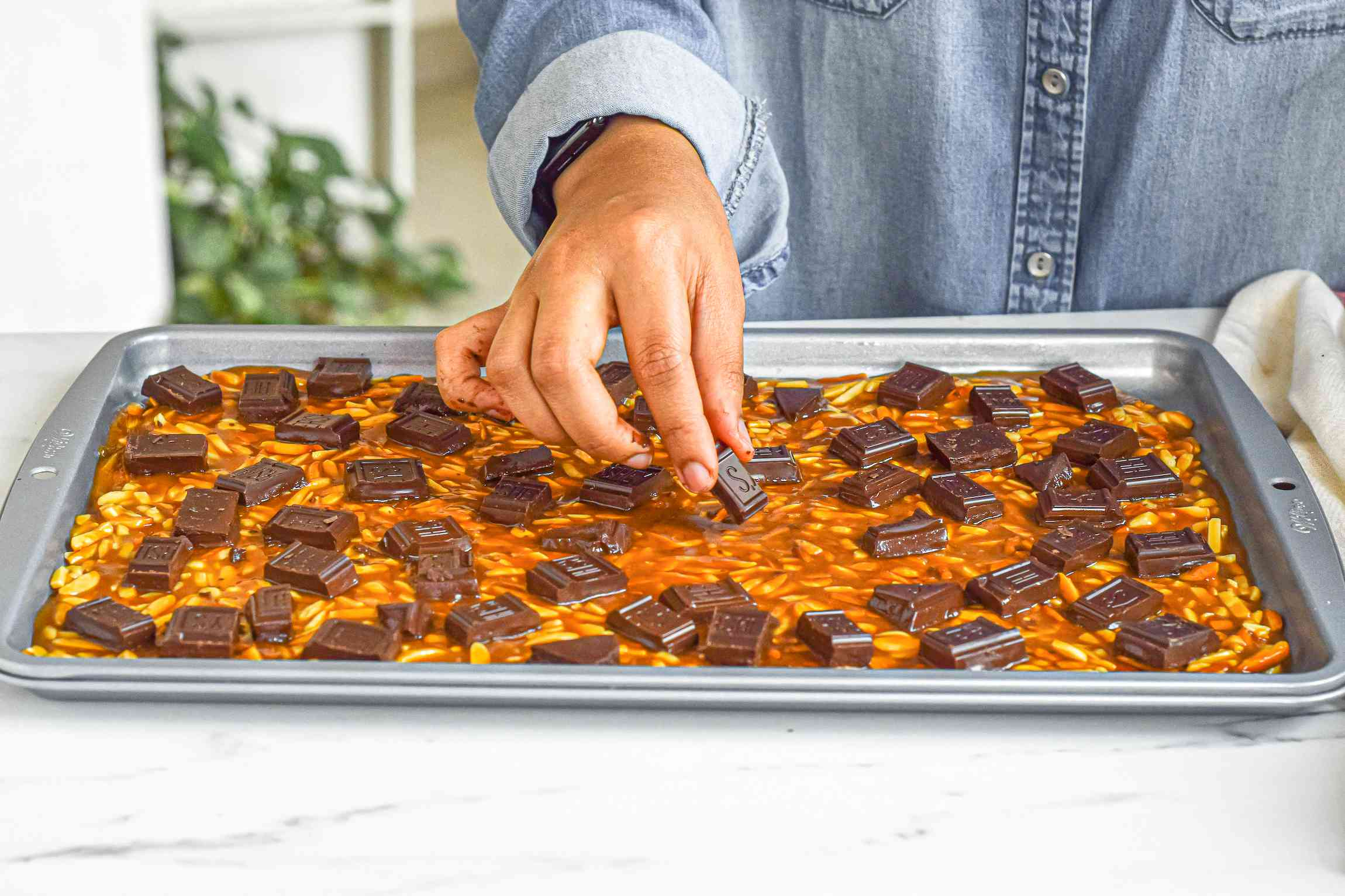 Adding chocolate to the top of the almond roca candy.