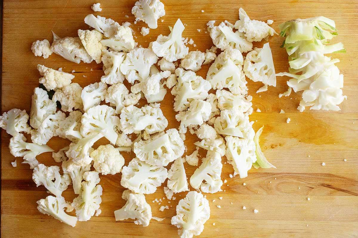 Chopped raw cauliflower on a wooden cutting board.
