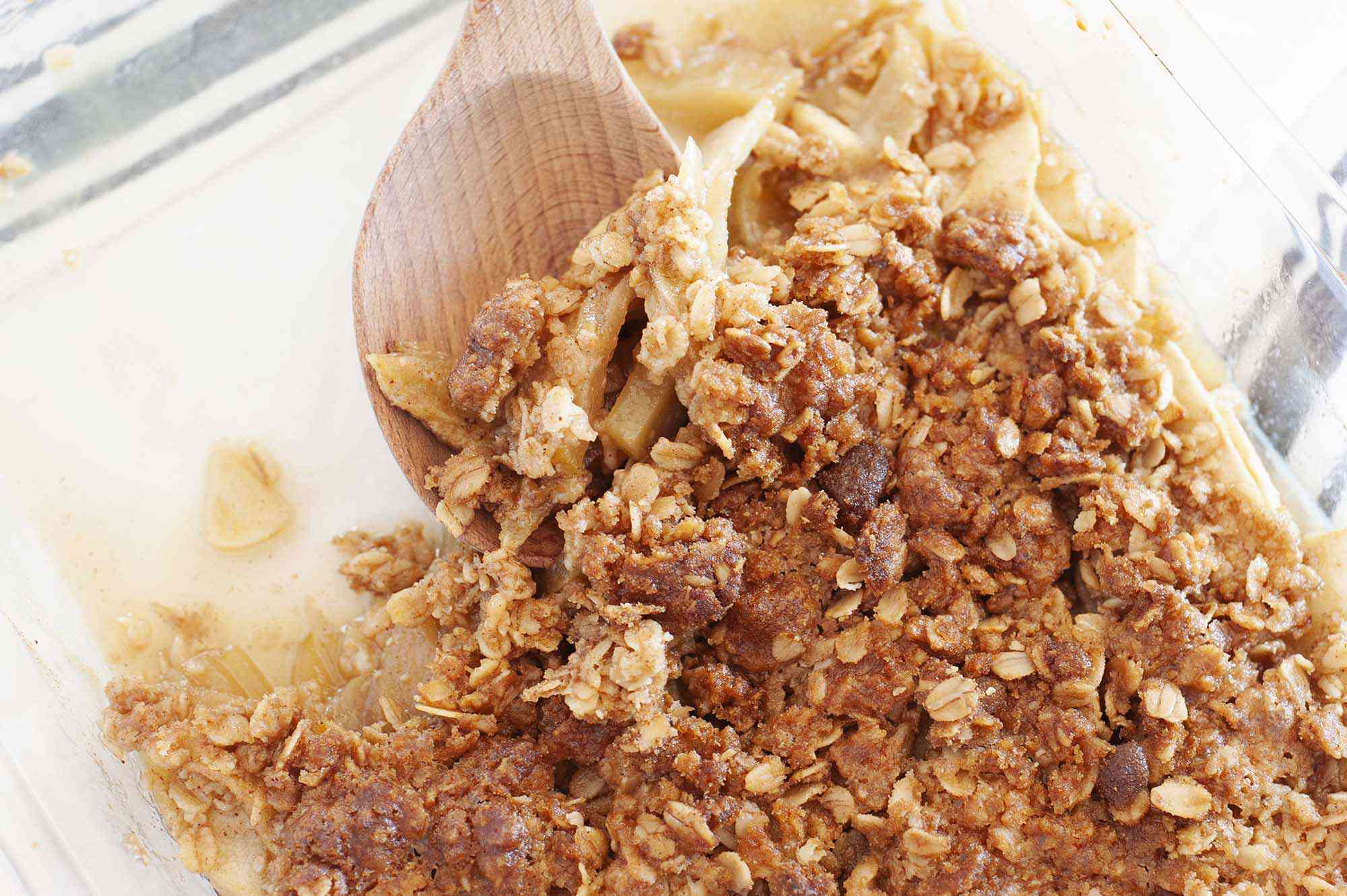 Apple crisp topping stirred with a wooden spoon.