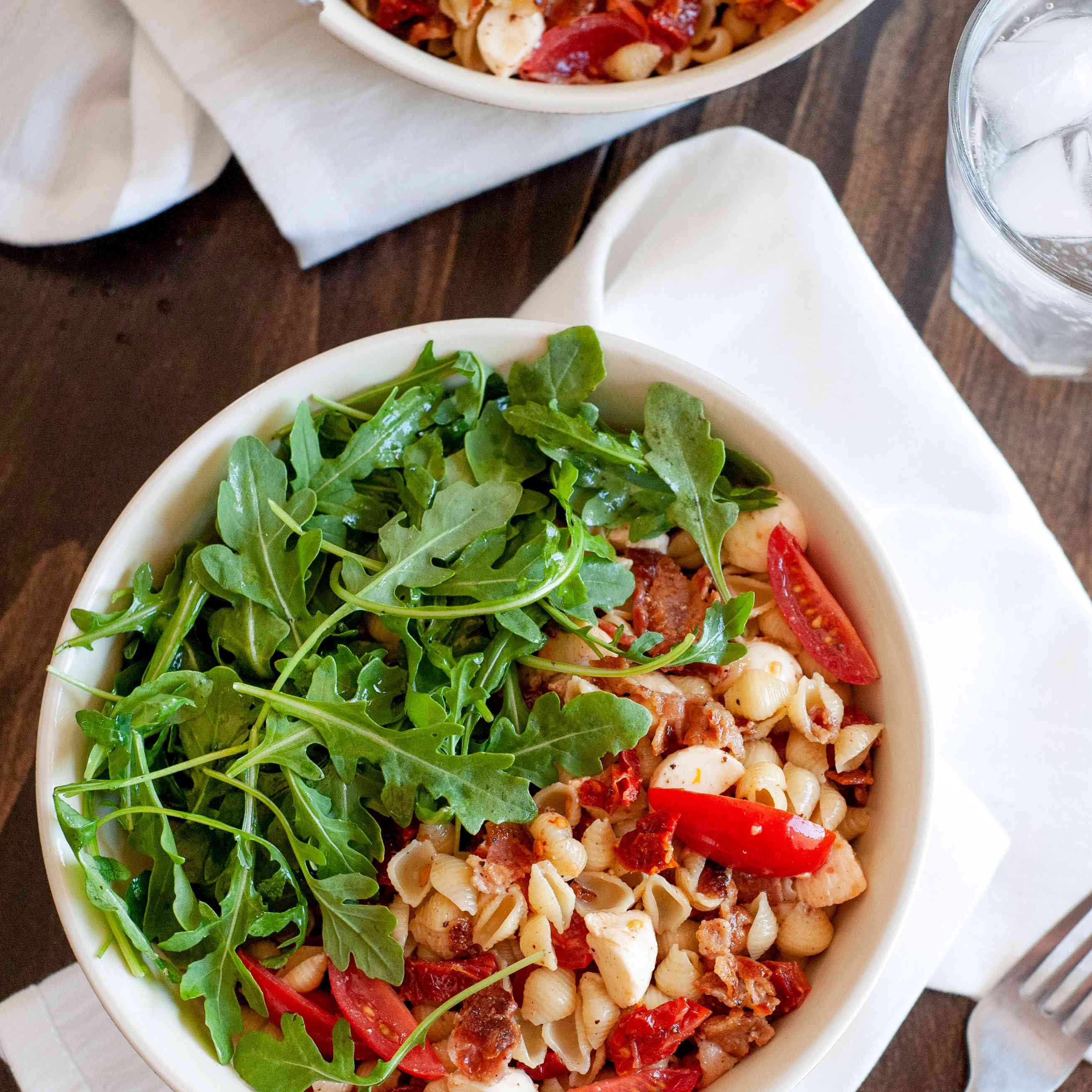 Bacon, tomato, and arugula pasta viewed overhead in a white bowl.