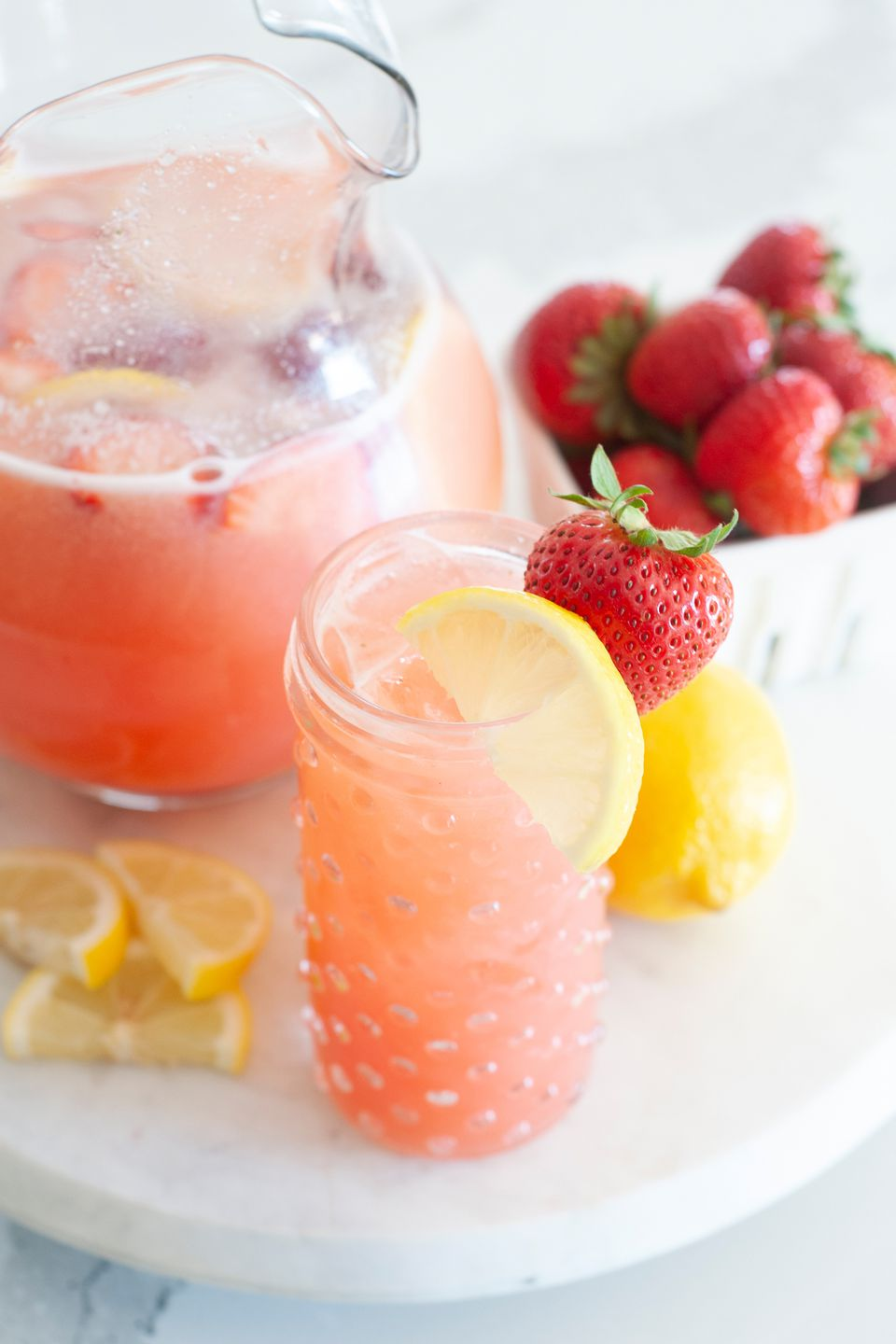 A round platter with a glass and pitcher of blender strawberry lemonade.