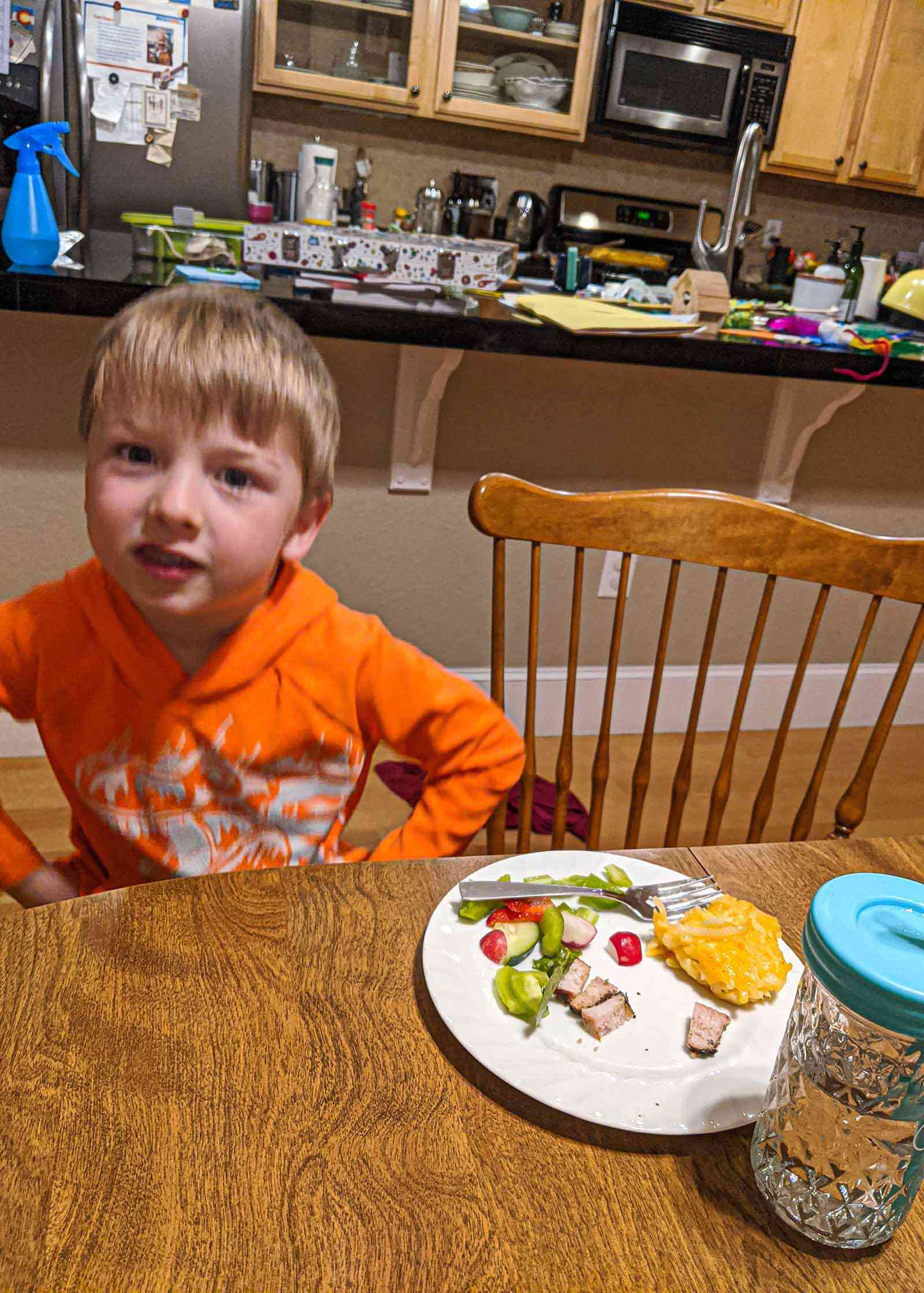 Preschool boy sitting at the kitchen table with a white plate of food in front of him The plate has a scoop of cheesy funeral potatoes, chopped ham, a salad and a fork. The kitchen is in the background of the picture.