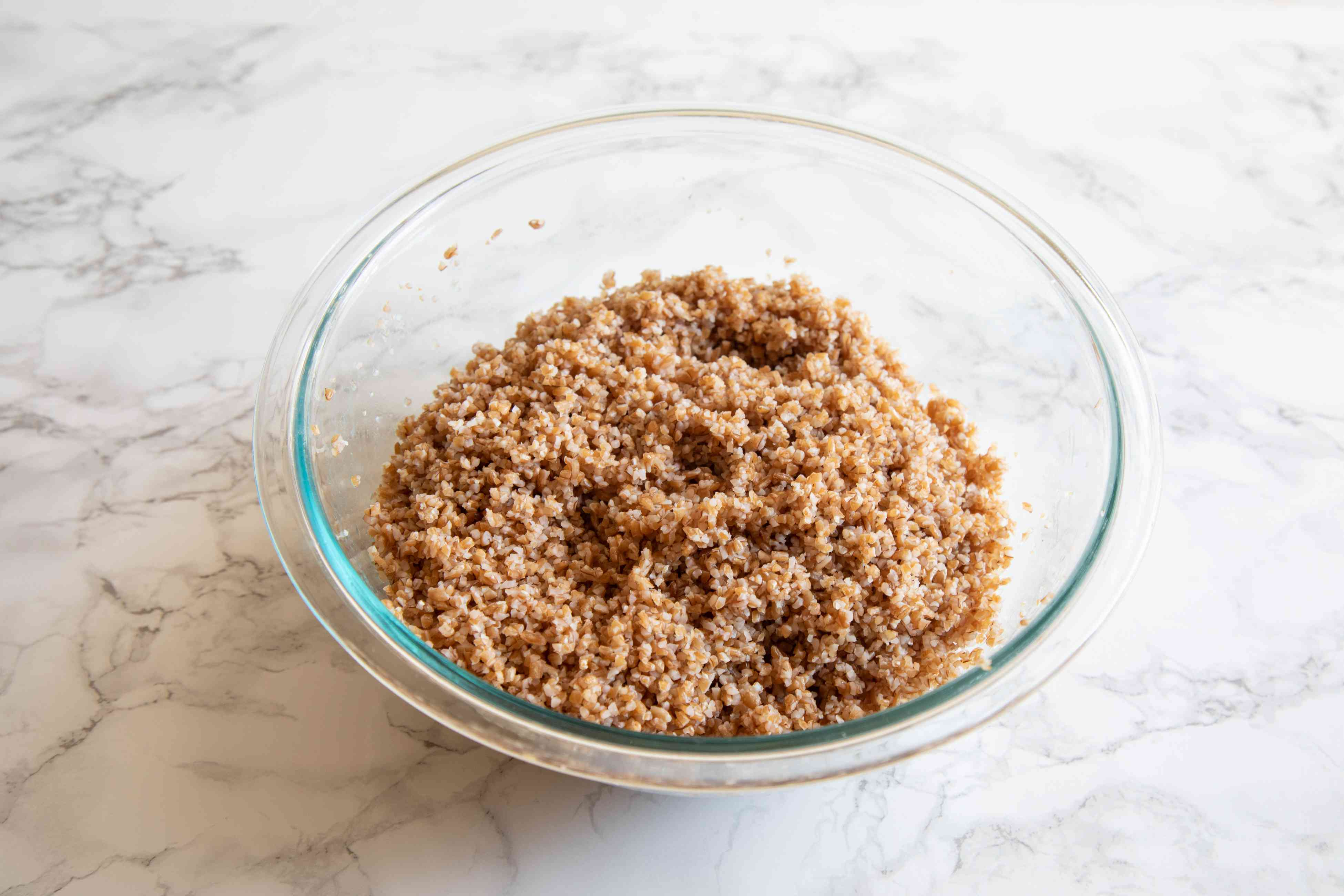 A glass bowl with bulgur to make a tabbouleh recipe.
