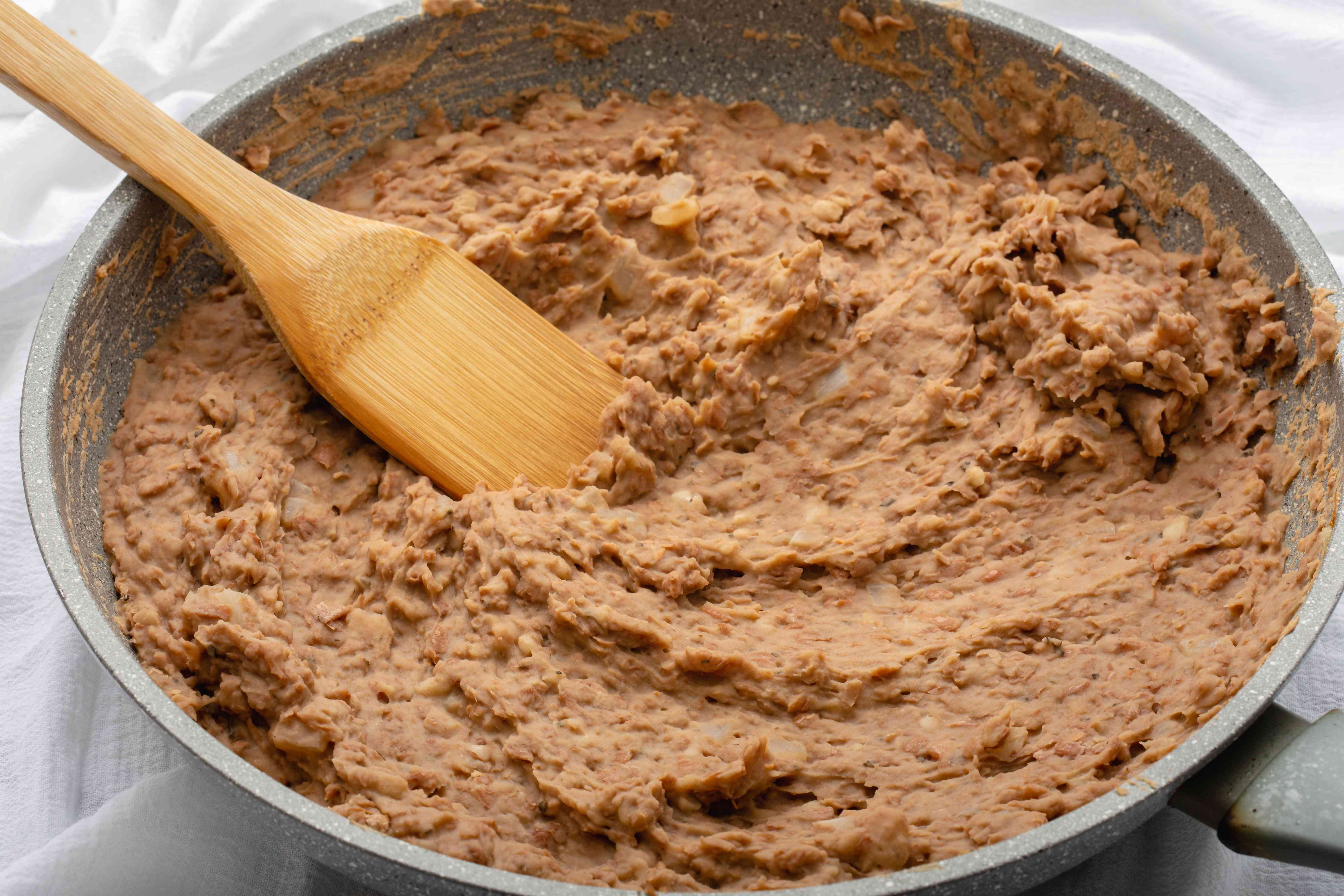 A large bowl of homemade refried beans and a wooden utensil.