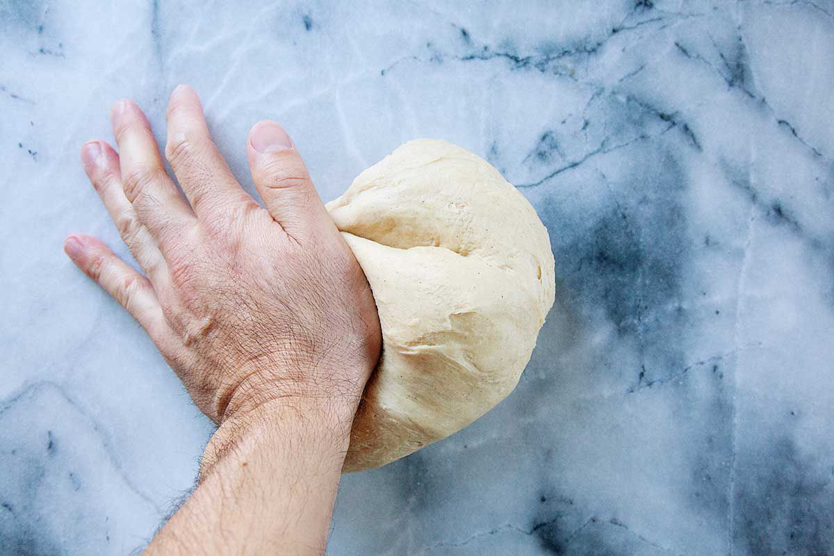 A hand is kneading king cake dough on a marble background.