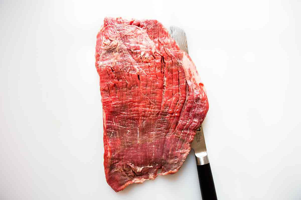 knife positioned in the same direction of the grain of the meat of flank steak
