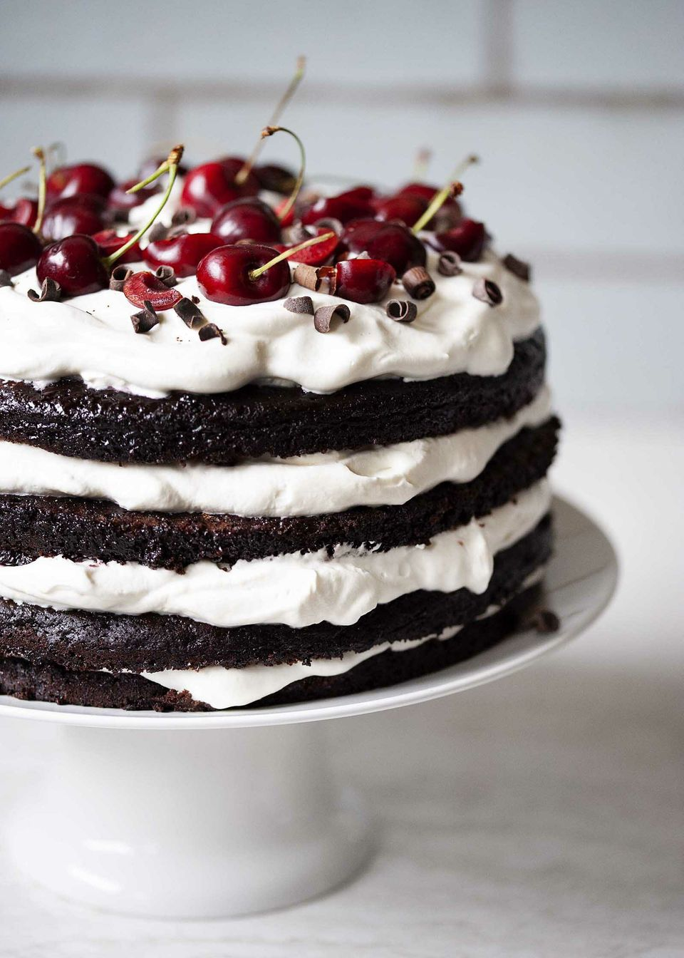 Authentic Black Forest Cake on a cake stand and topped with fresh cherries and chocolate.