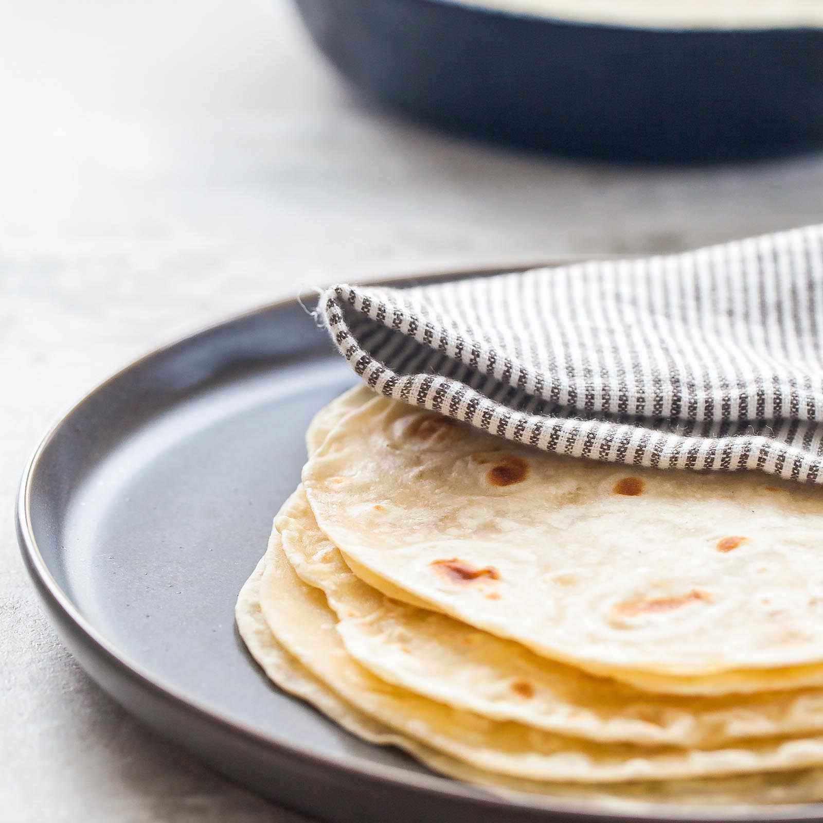 A stack of homemade flour tortillas on a platter covered by a striped towel. A cast iron skillet with another tortilla inside is in the background.