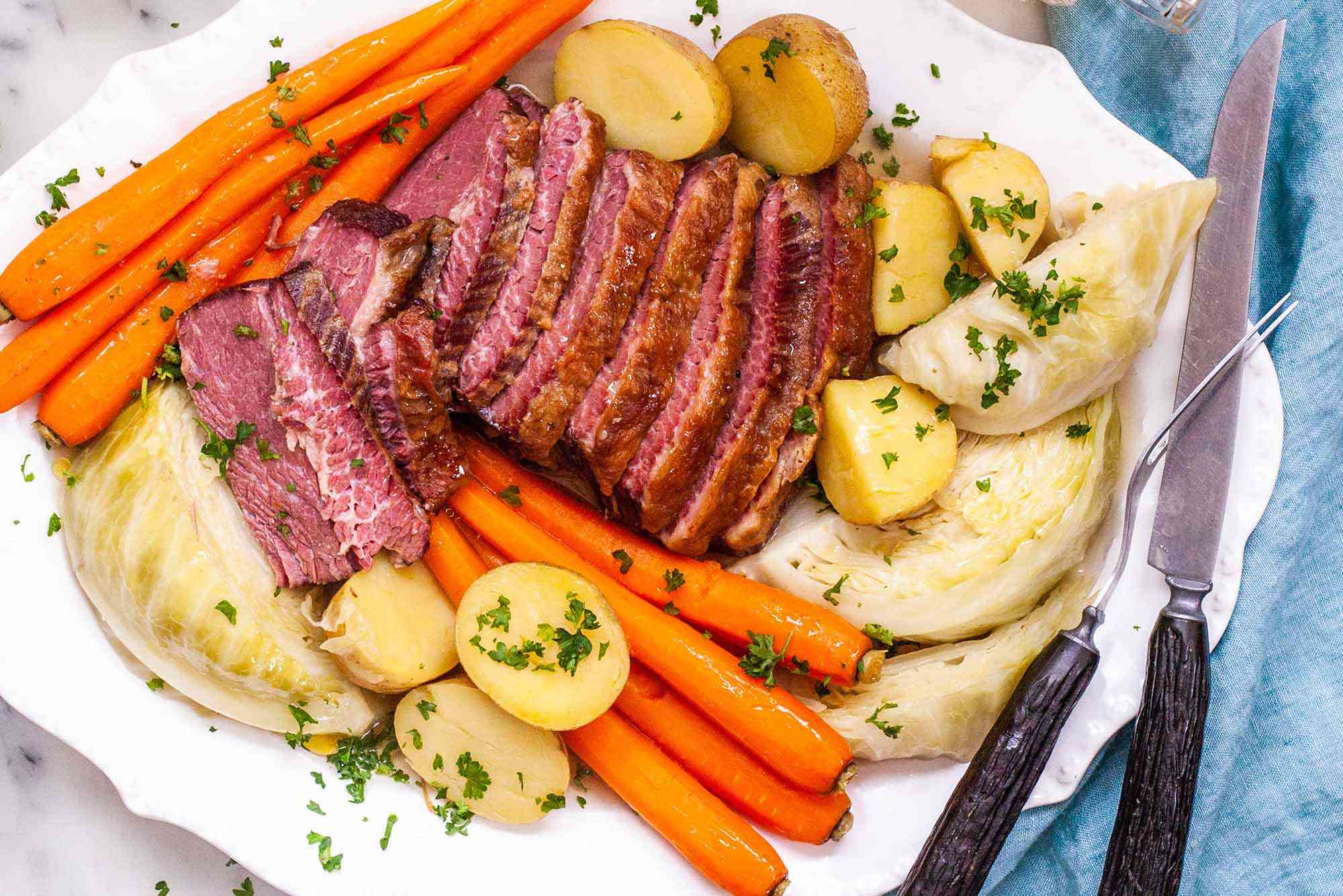 Best Boiled Corned Beef and Cabbage Recipe - platter of sliced corned beef, carrots, potatoes, and cabbage sprinkled with herbs
