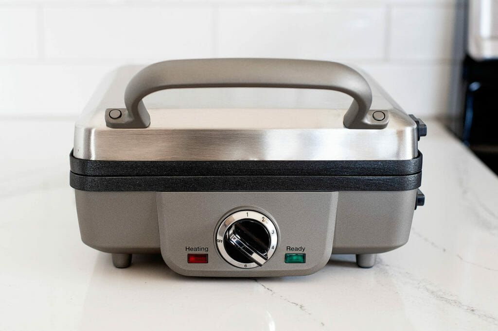 A closed waffle maker that is not plugged in and neither light is on.