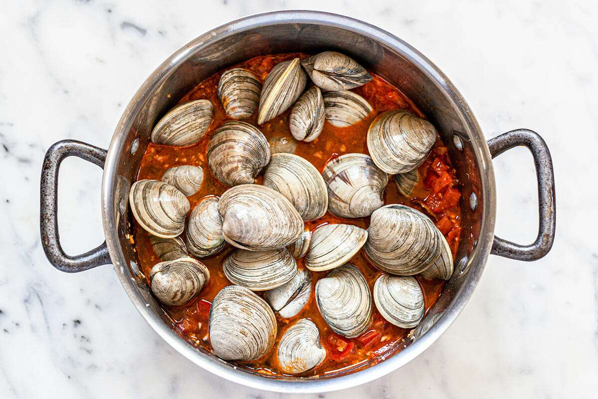 Overhead view of a large stockpot with tomato broth and closed clams on top.