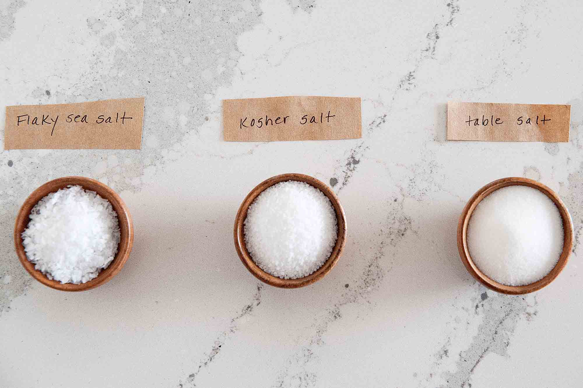 Three wooden bowls filled with kosher salt, table salt and flaky sea salt