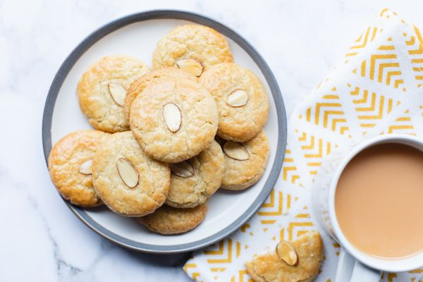 Overhead view of a plate of Chinese almond cookies and a mug.