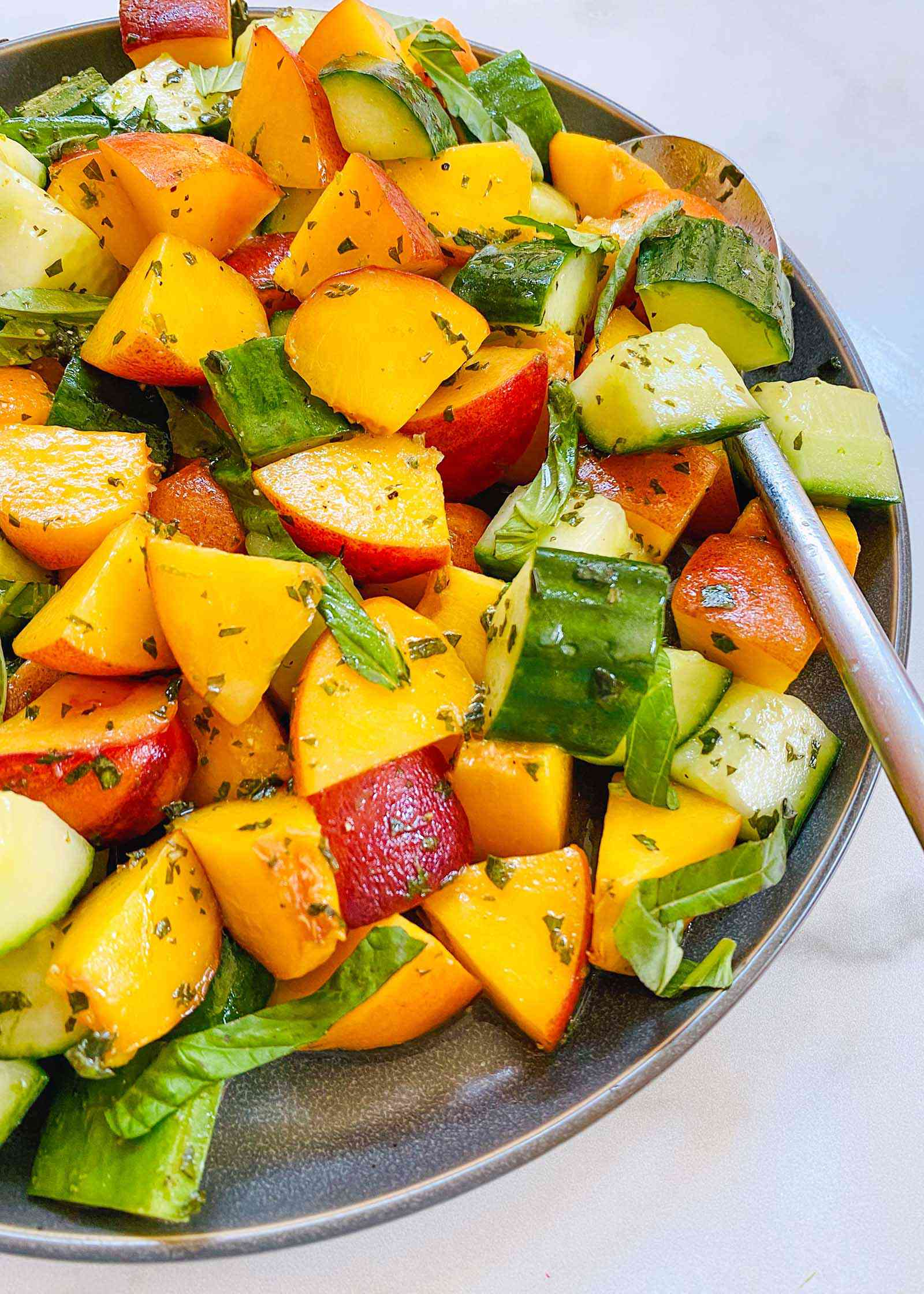 Close up of a bowl of peach and cucumber salad.