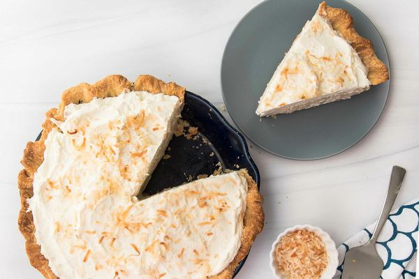Overhead view of a homemade coconut cream pie with a slice removed and set on a plate to the right.