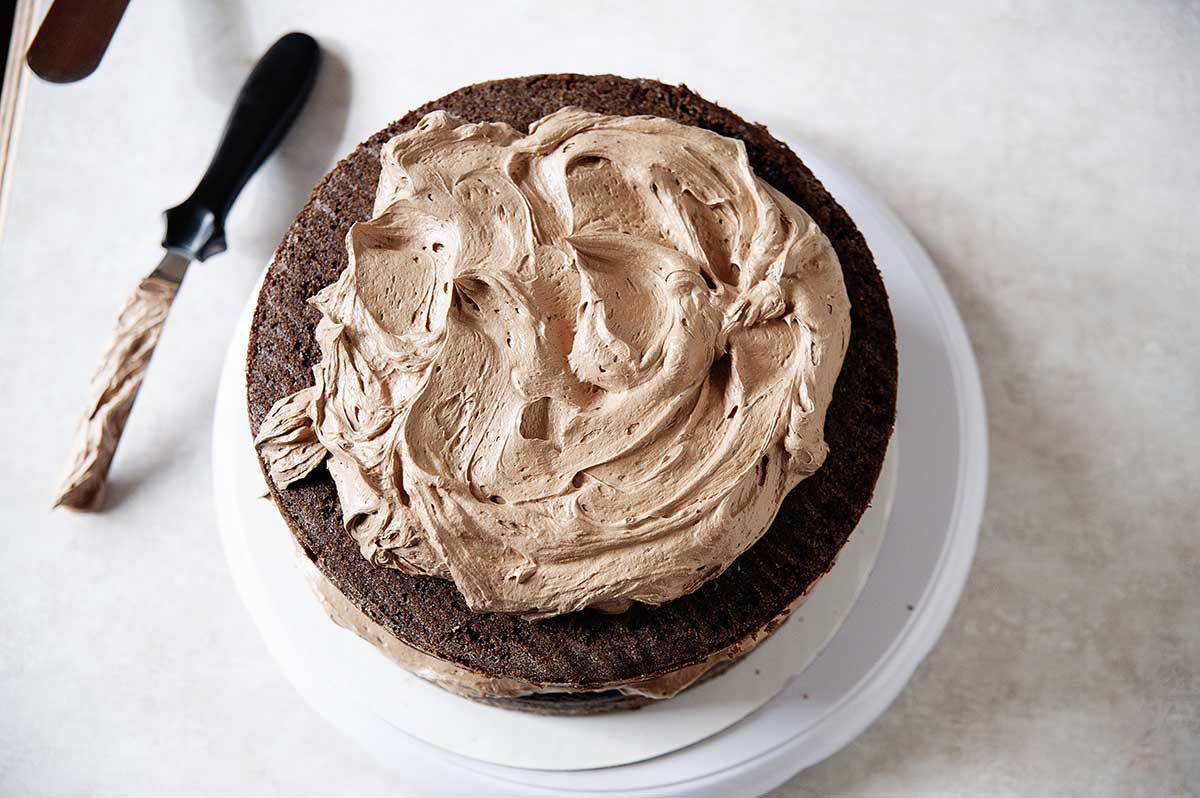 Woman using an offset spatulat to smooth creamy chocolate swiss meringue buttercream frosting on top of the best chocolate buttermilk layer cake