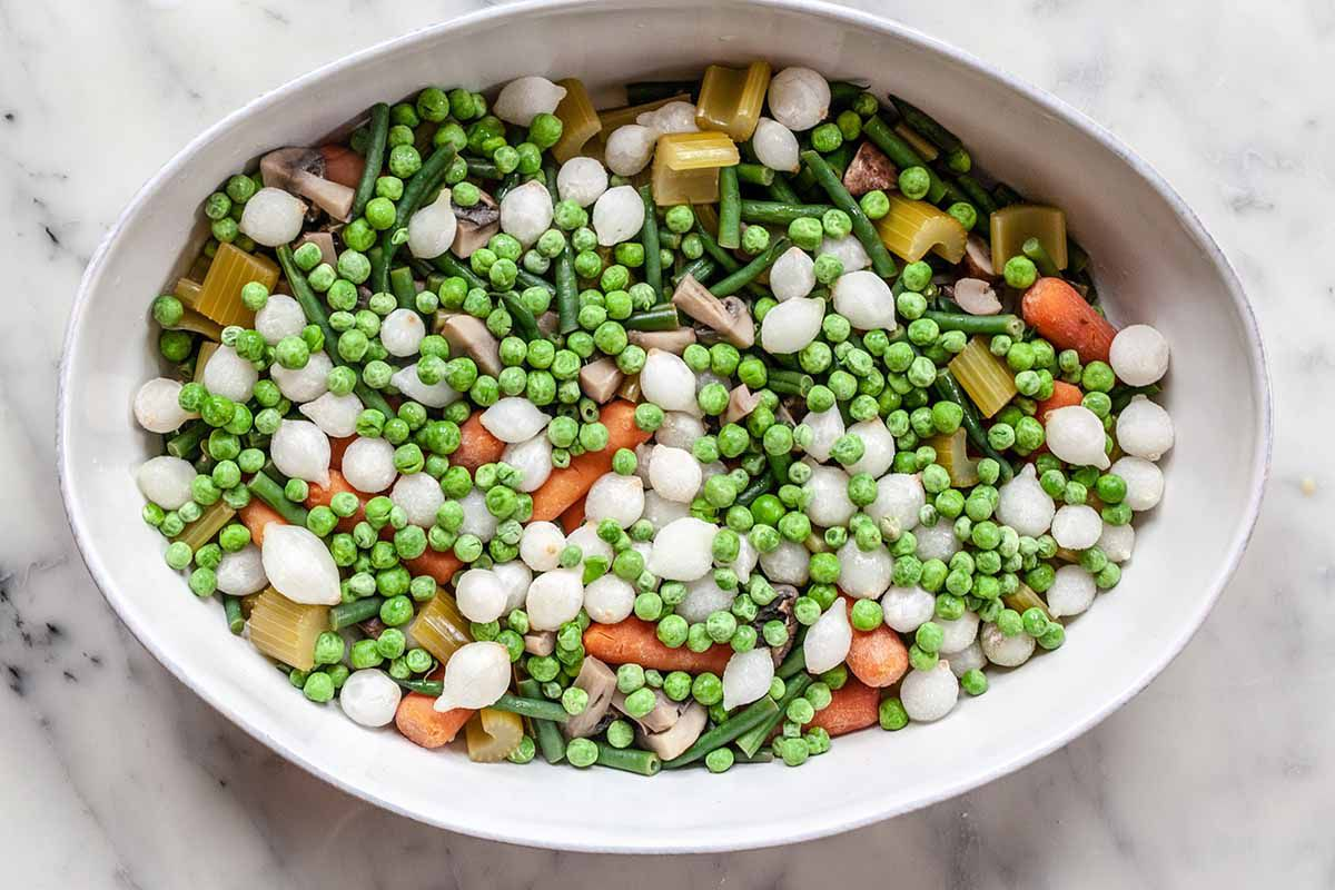 Vegetarian Shepherd's Pie Recipe -- white casserole dish filled with carrots, peas, onions, mushrooms