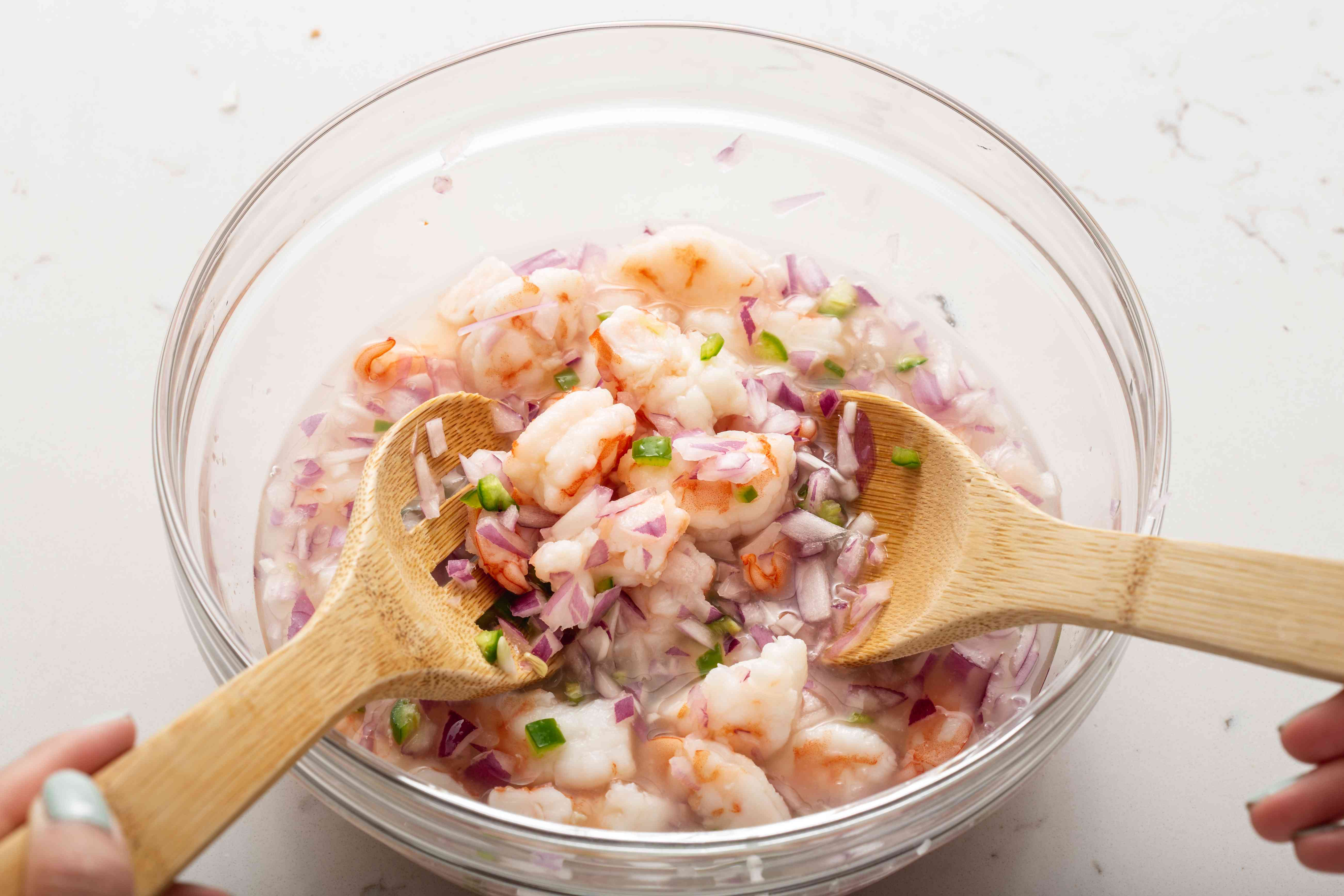 Mixing ingredients to show how to make shrimp ceviche.