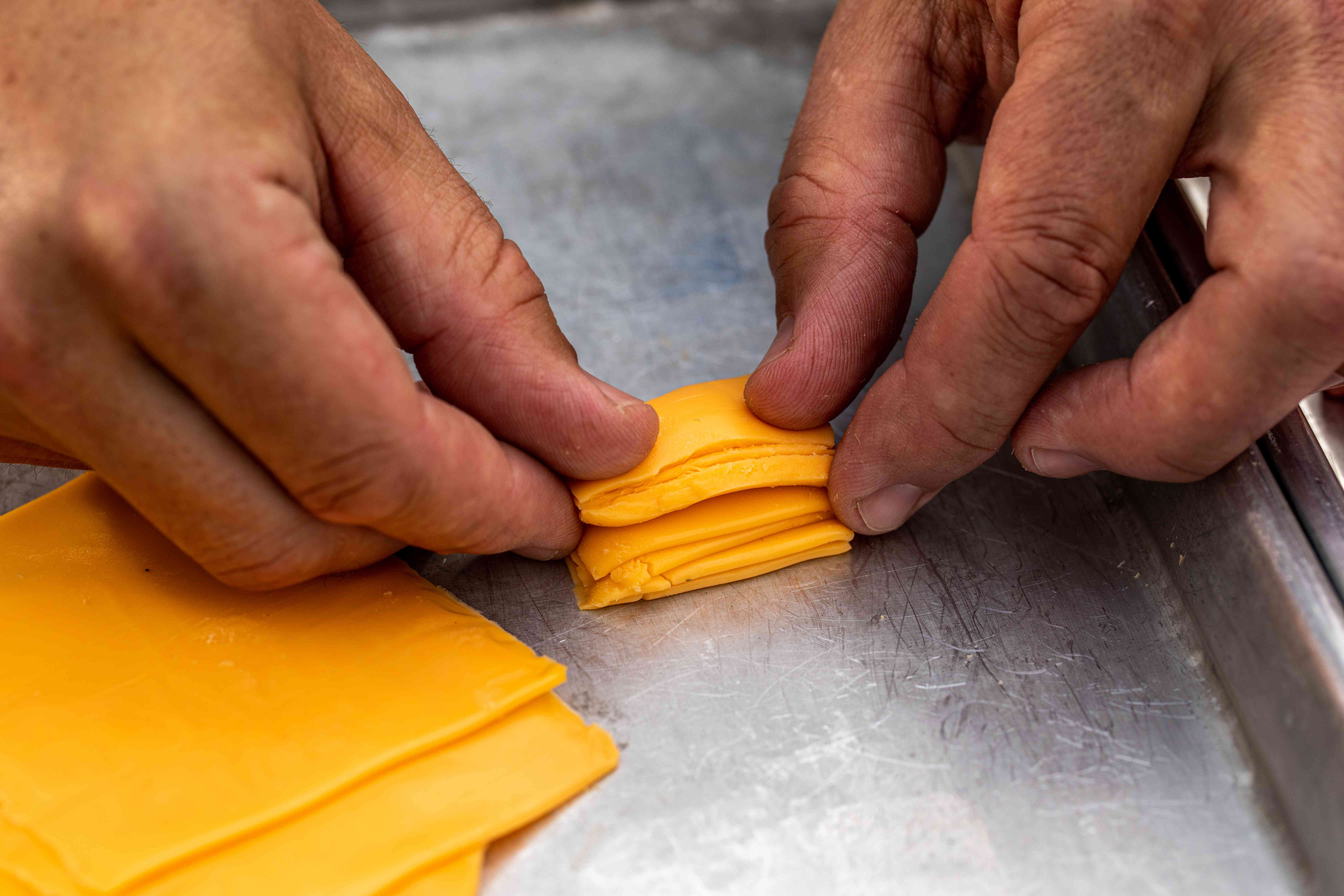 Folding sliced cheese to show how to make a Jucy Lucy burger