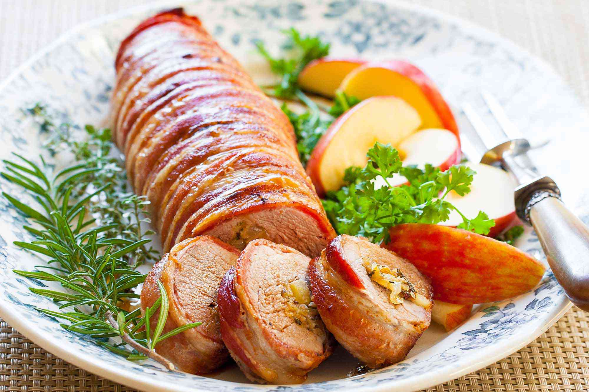 bacon wrapped pork loin served on platter with apples