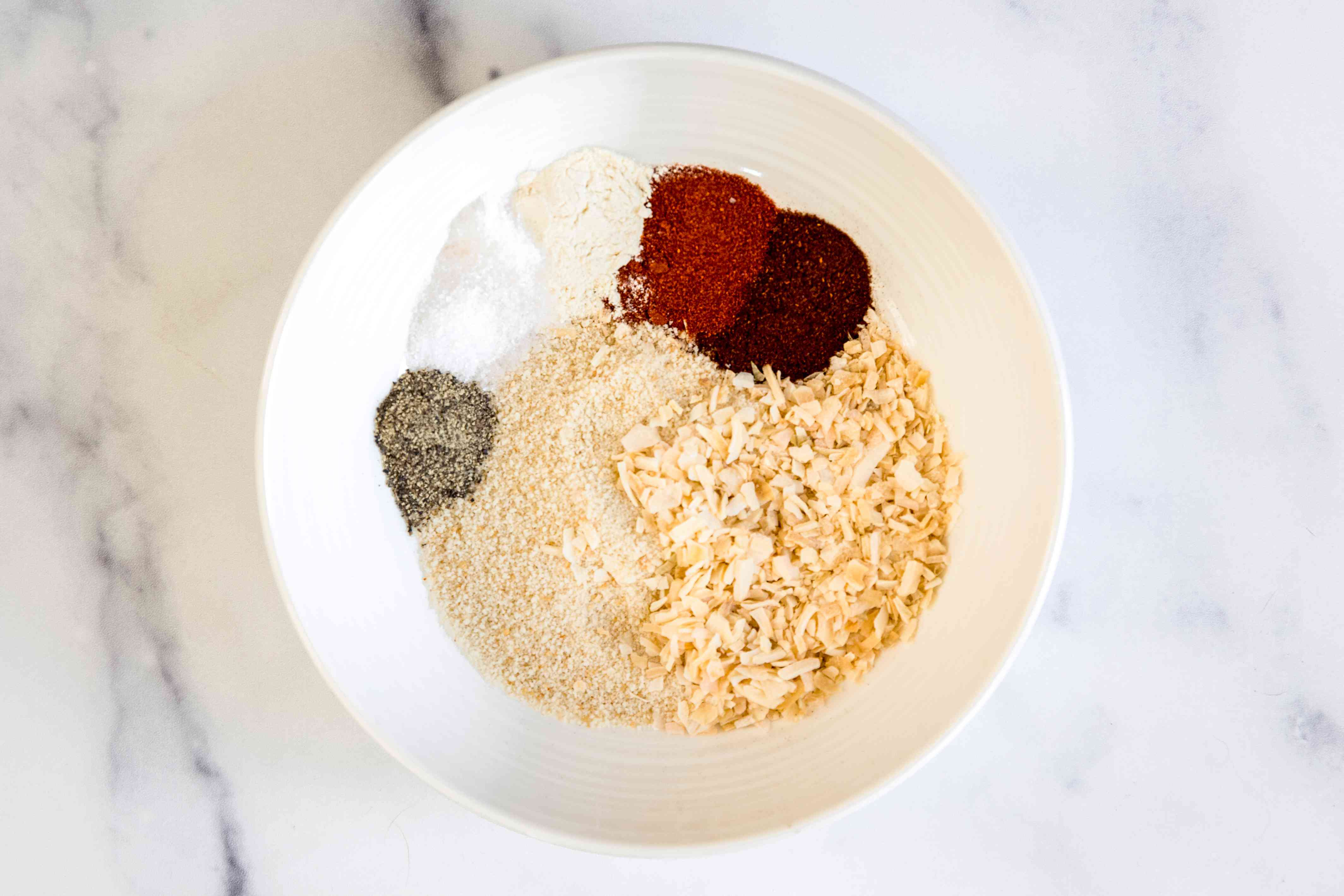 Spices and breadcrumbs in a bowl to make mini meatloaves with veg and potatoes in a sheet pan.