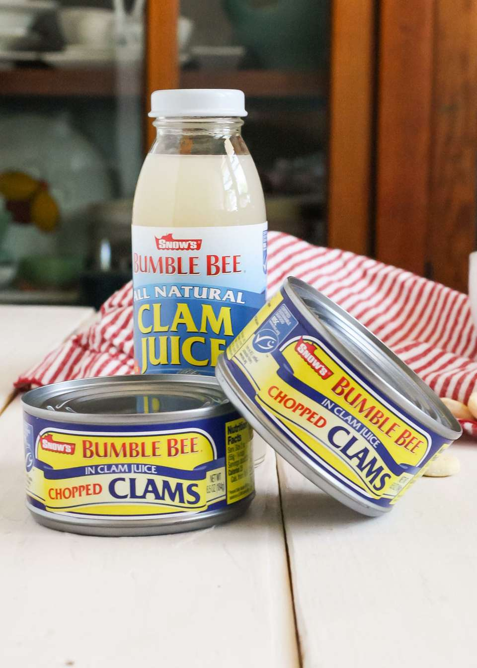 Two cans of clams and a bottle of clam juice set on a table. Why you should buy canned clams