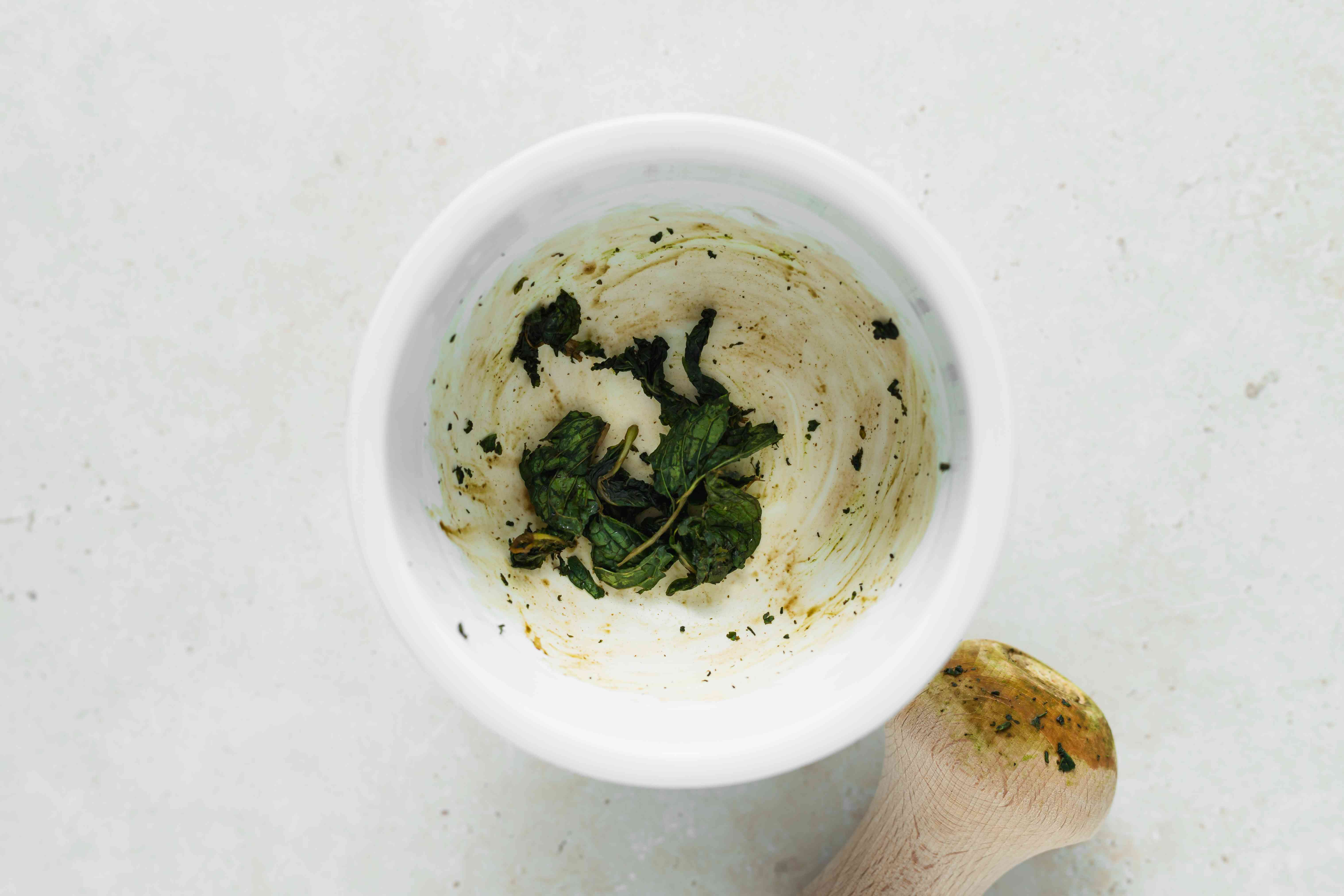 Mashing mint in a bowl for a wax beans recipe.