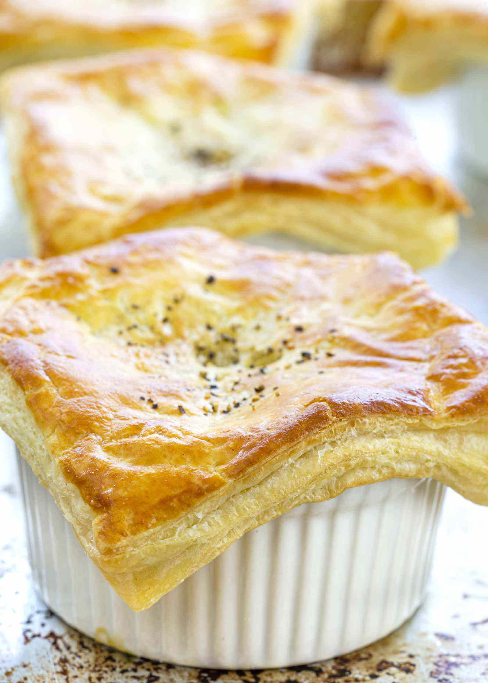 Vegetable pot pie on white plate with puff pastry on top.